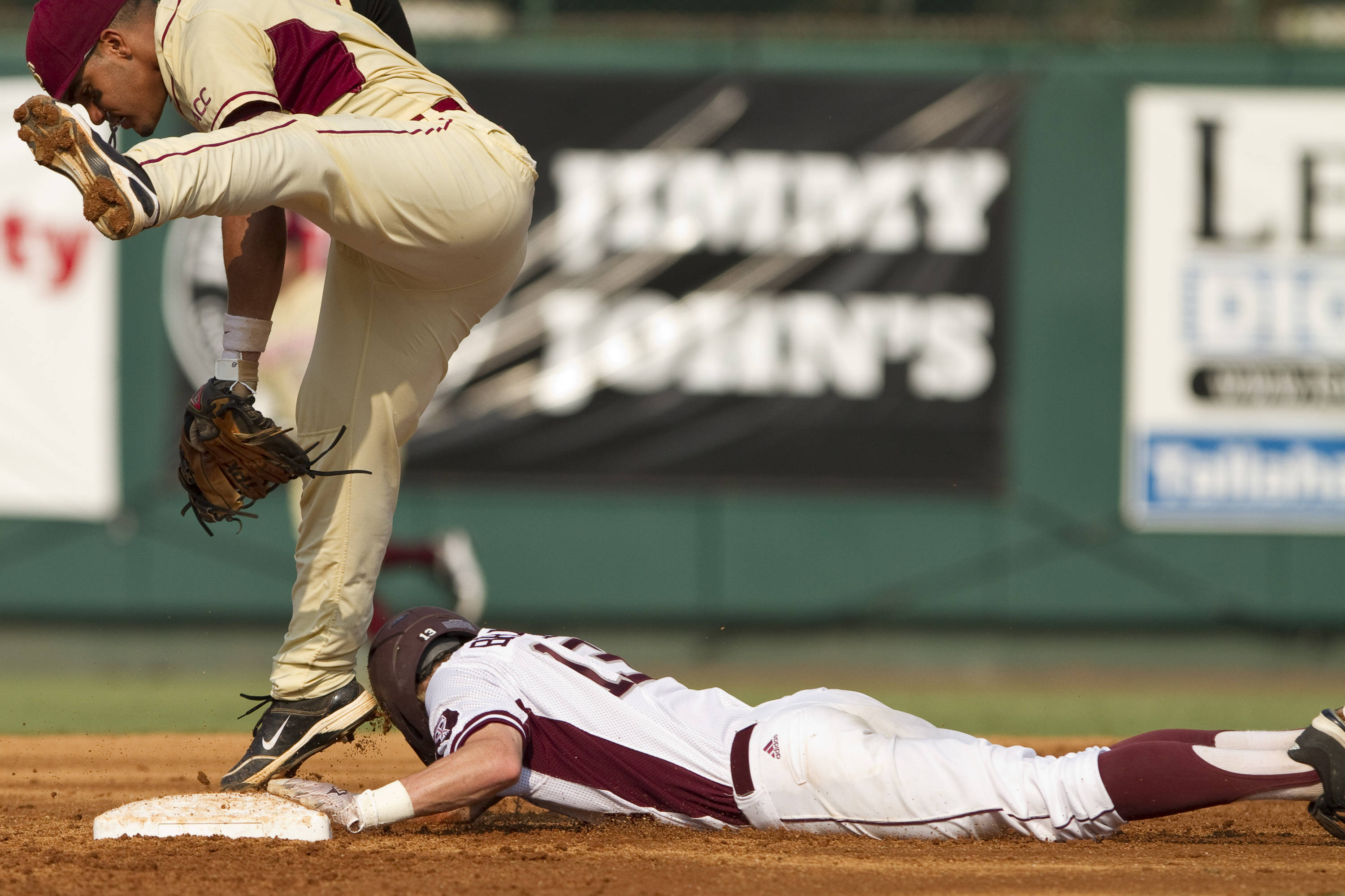 Devon Travis (8) attempts to tag a runner after jumping to catch a high ball.
