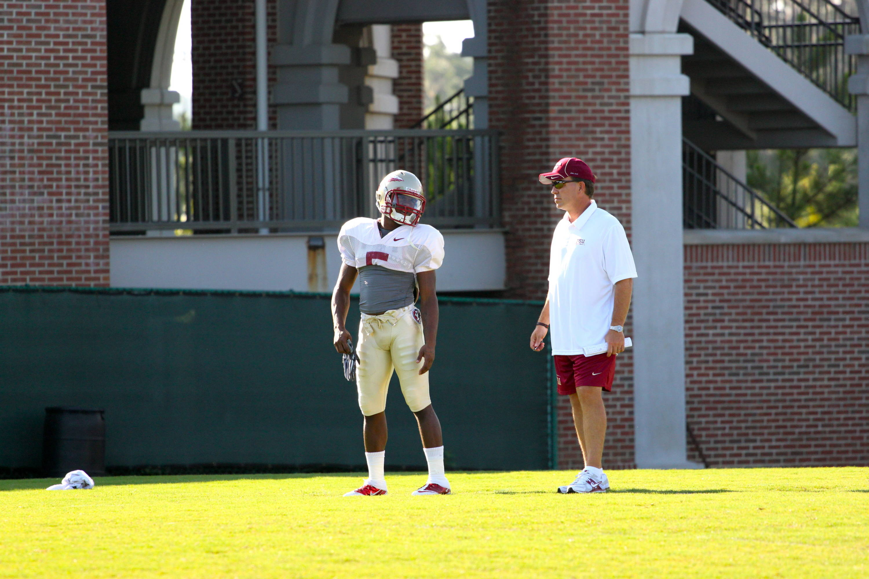 Greg Reid (5) and Jimbo Fisher talk during a punt drill