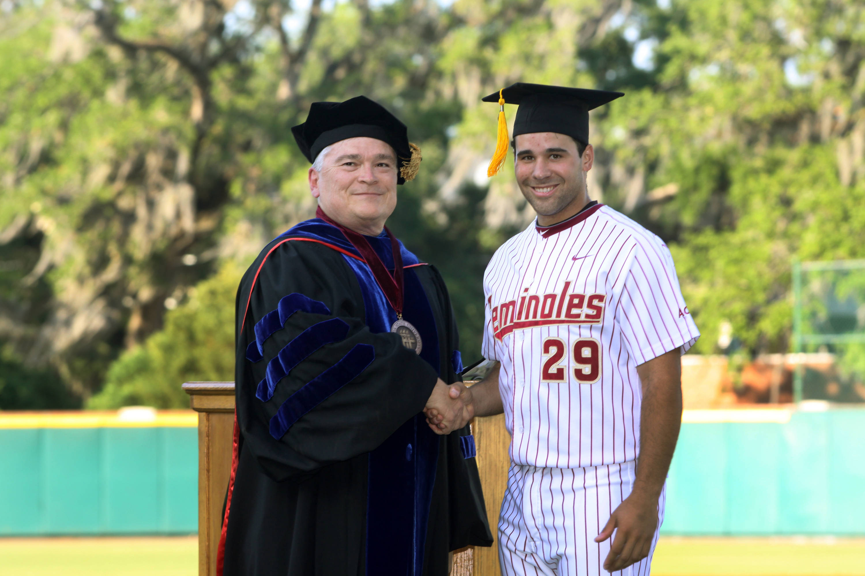 2011 Spring Graduation Ceremony held at Dick Howser Stadium to honor the graduating baseball seniors. Rafael Lopez (29) with President Barron