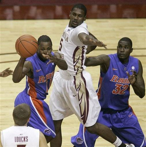 Florida's Erving Walker passes after trying to penetrate the defense of Florida State's Bernard James as teammate Vernon Macklin, right watches.(AP Photo/Steve Cannon)