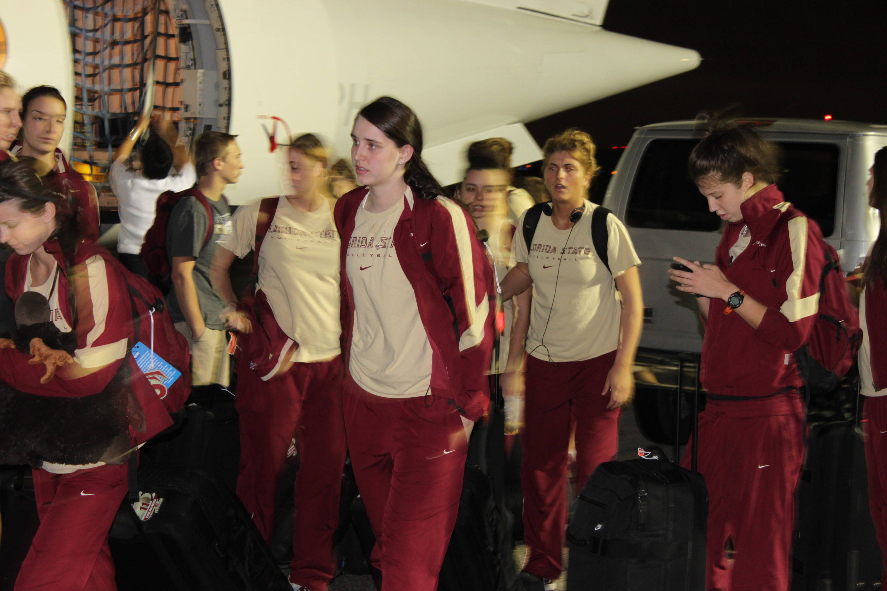 The student-athletes wait outside the charter plane before heading to their hotel