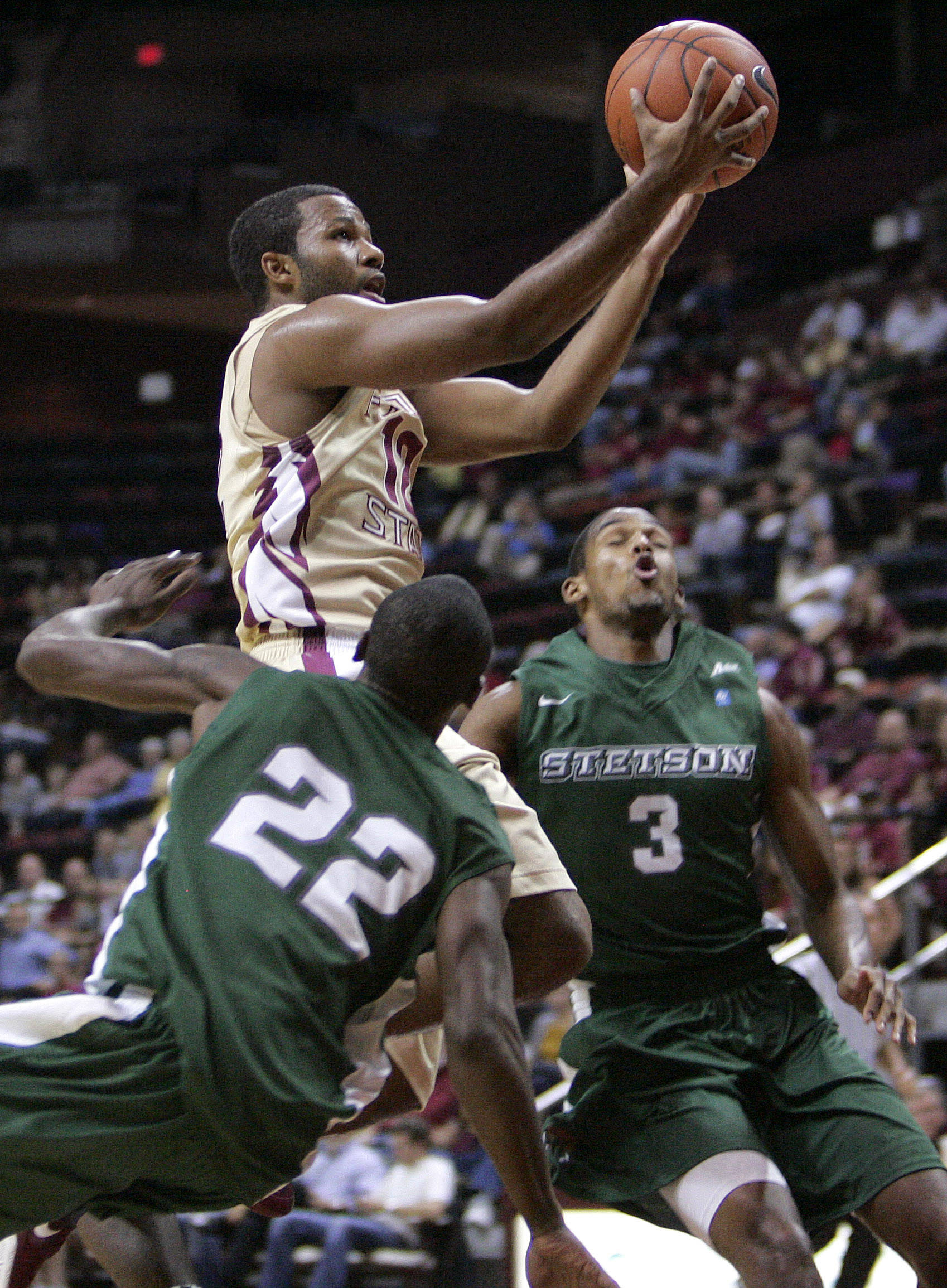 Florida State's Jeff Peterson, top, splits the defense of Stetson's Tyshawn Patterson and Willie Green on his way to the hoop. (AP Photo/Steve Cannon)