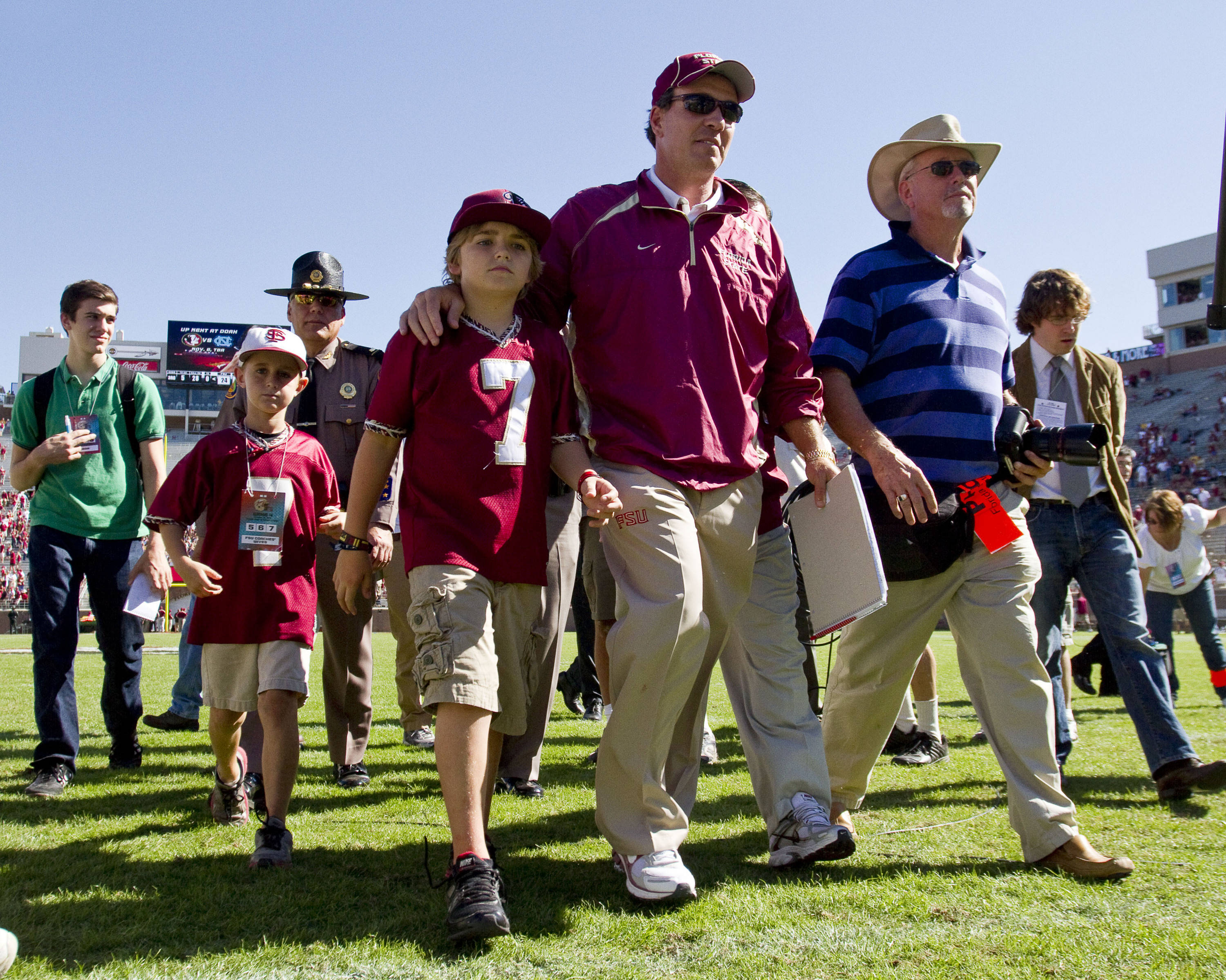 Jimbo Fisher walks off the field with his son.