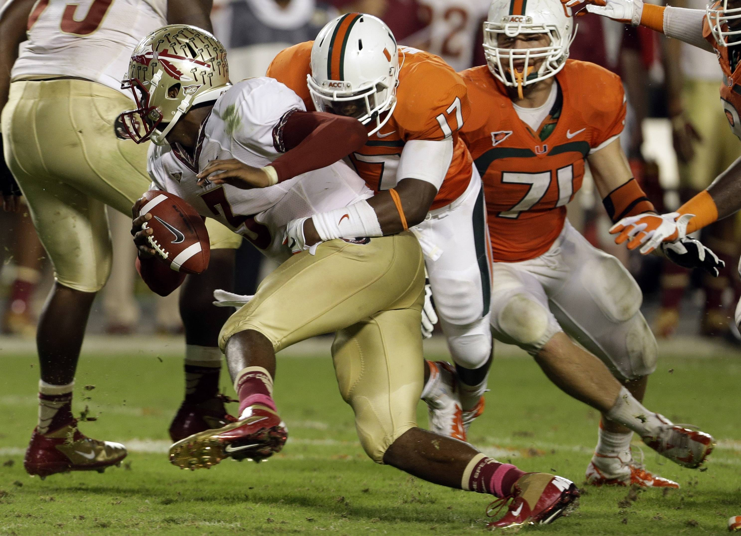 Florida State quarterback EJ Manuel, front left, is tackled by Miami defensive lineman Tyriq McCord (17) during the second half of an NCAA college football game on Saturday, Oct. 20, 2012, in Miami. (AP Photo/Lynne Sladky)