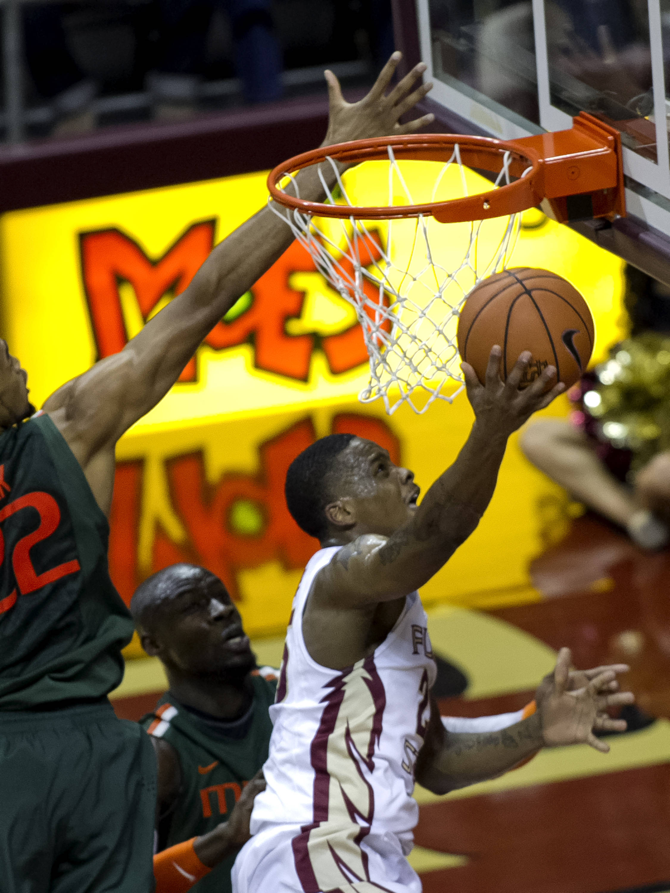 Aaron Thomas (25) uses the rim for protection, FSU vs Miami, 2-10-14, (Photo's by Steve Musco)