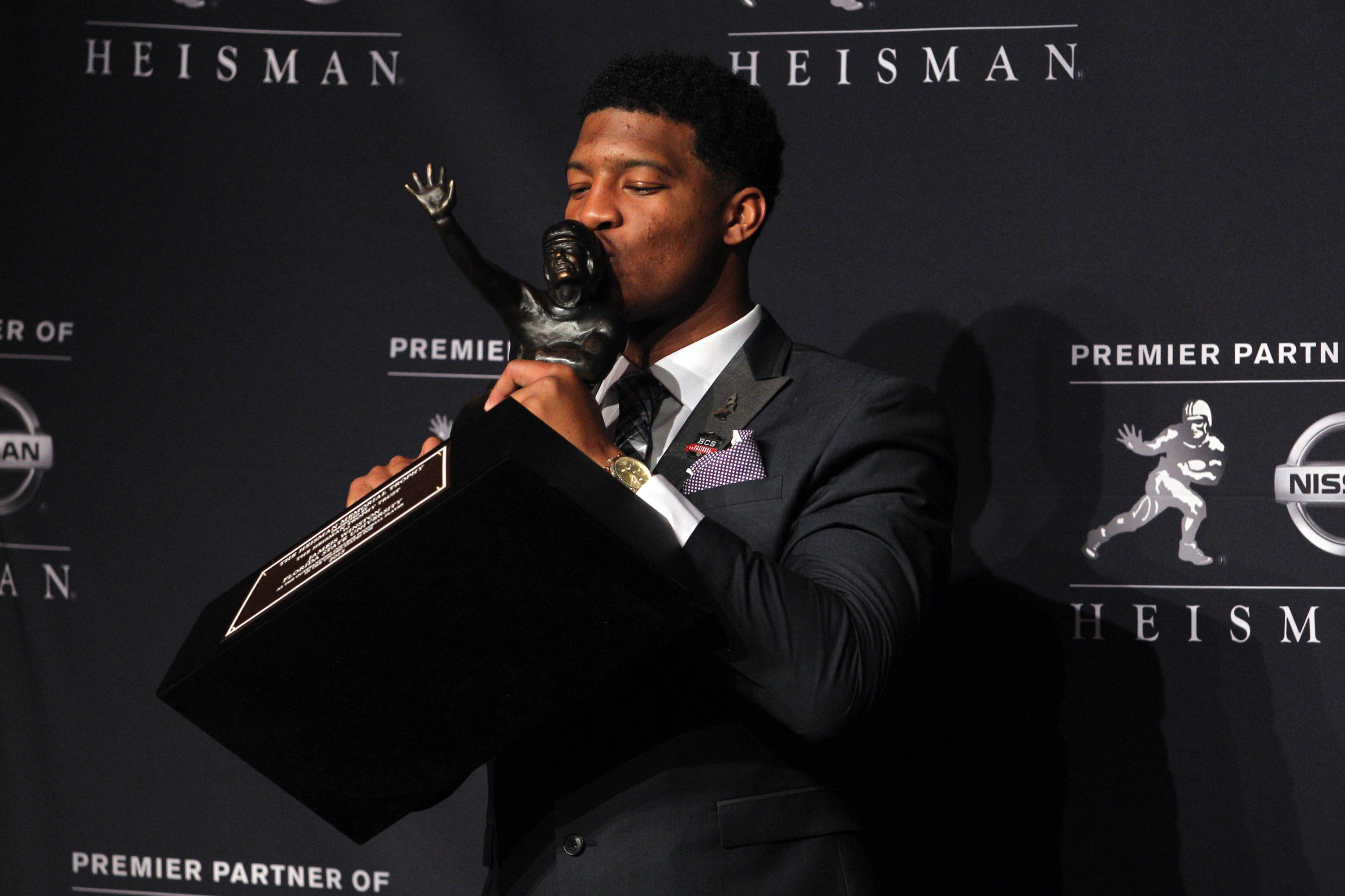 Dec 14, 2013; New York, NY, USA; Seminoles quarterback and 2013 Heisman Trophy winner Jameis Winston kisses the trophy during a press conference. Brad Penner-USA TODAY Sports