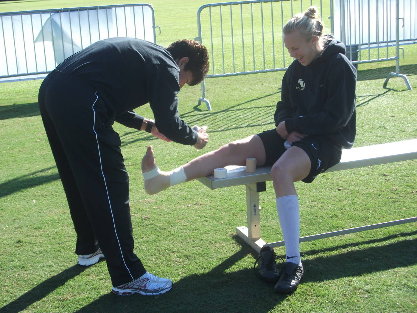Robin Gibson wrapping the ankle of Ella Stephan