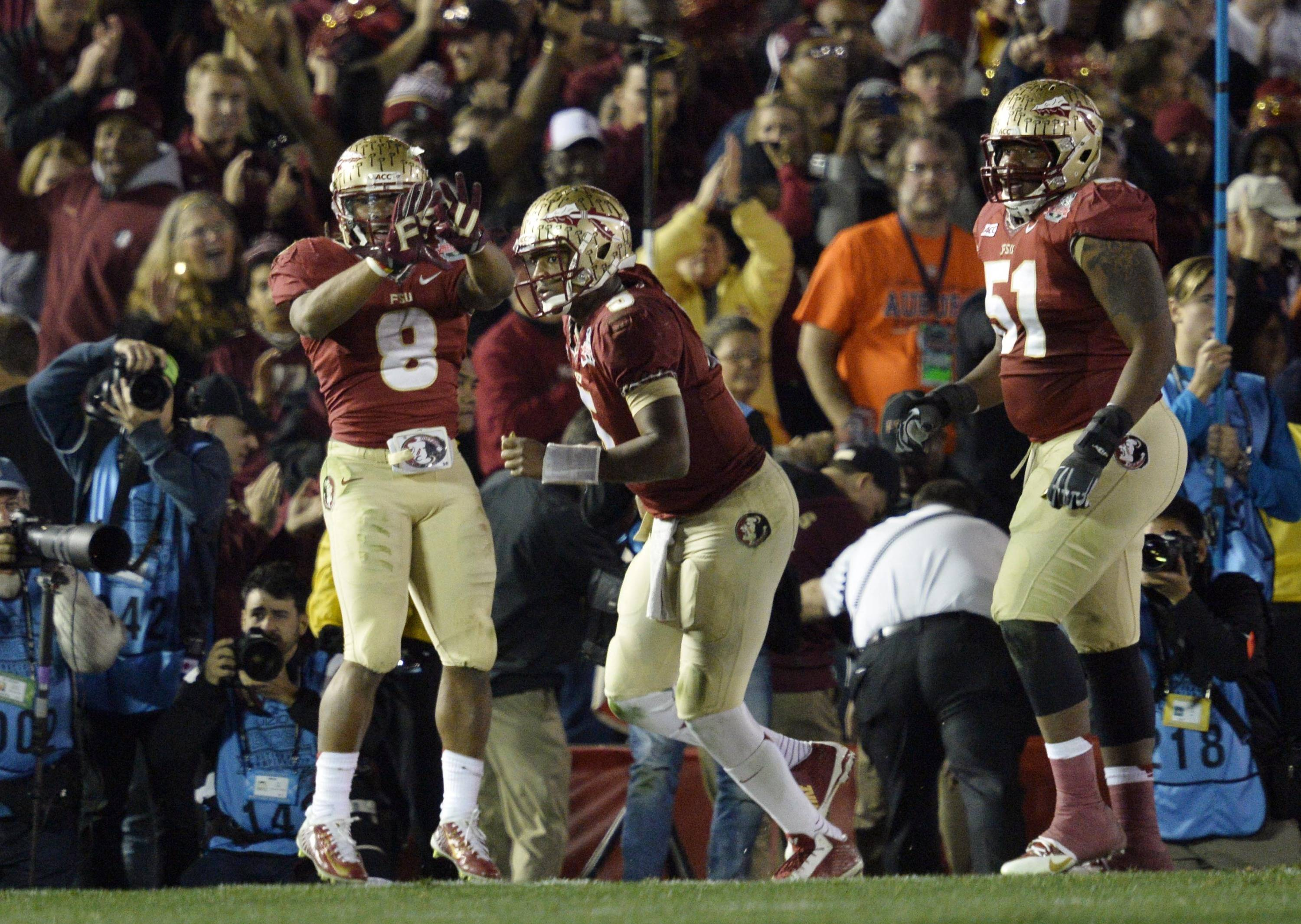 Jan 6, 2014; Pasadena, CA, USA; Florida State Seminoles running back Devonta Freeman (8) celebrates with teammates after scoring a touchdown against the Auburn Tigers during the first half of the 2014 BCS National Championship game at the Rose Bowl.  Mandatory Credit: Robert Hanashiro-USA TODAY Sports