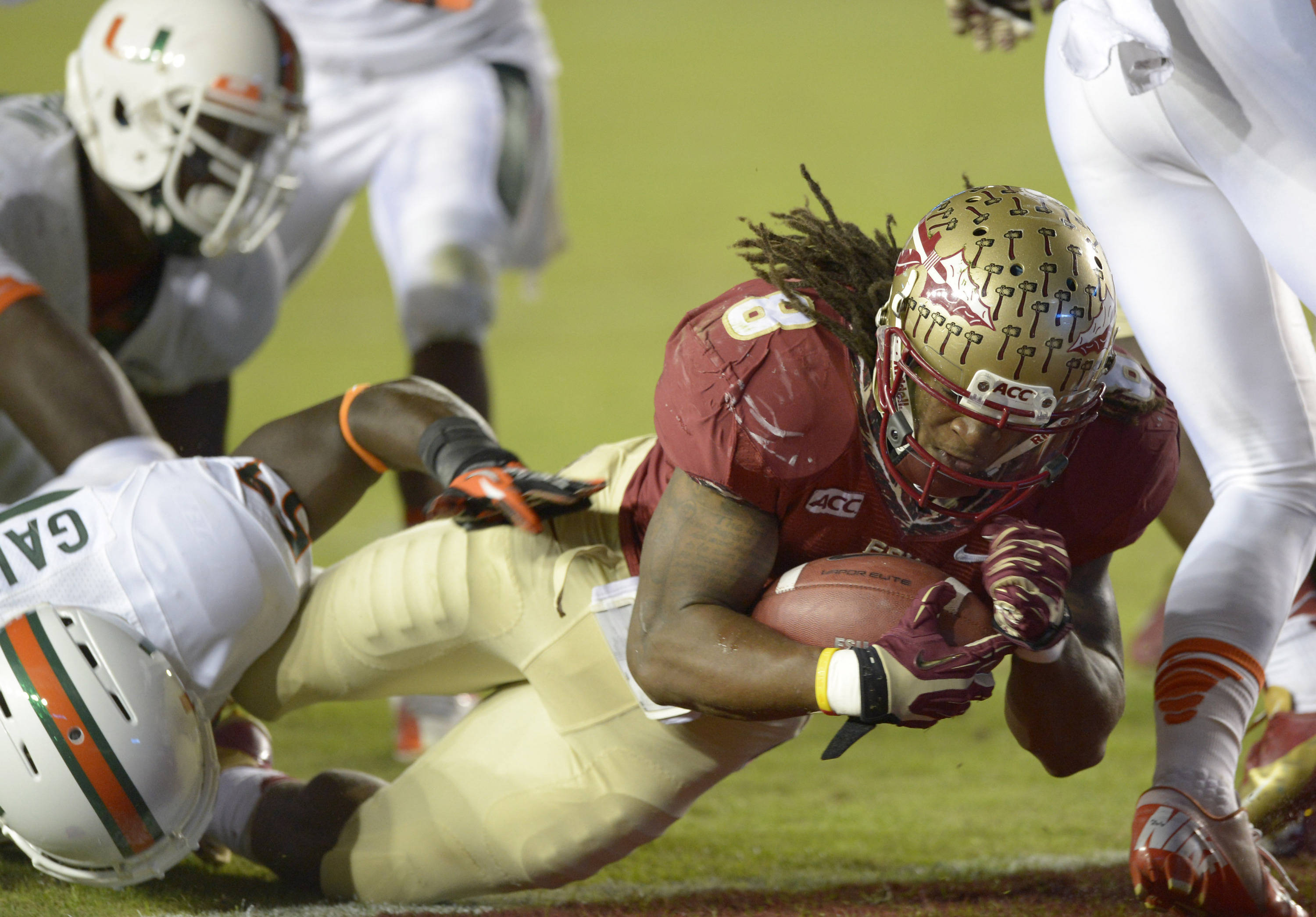 Florida State Seminoles running back Devonta Freeman (8) dives into the end zone for a touchdown against the Miami Hurricanes during the first quarter at Doak Campbell Stadium. Mandatory Credit: John David Mercer-USA TODAY Sports