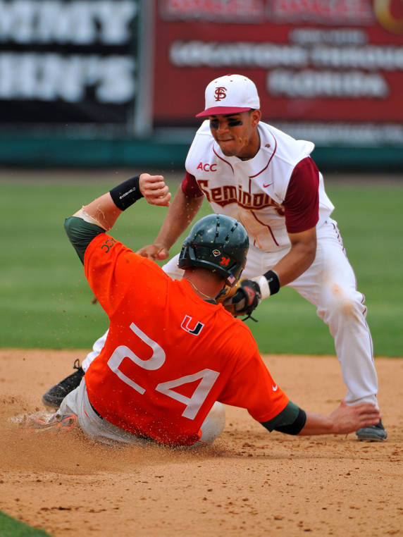 Devon Travis tags out Miami's Yasmani Grandal trying to steal second base.