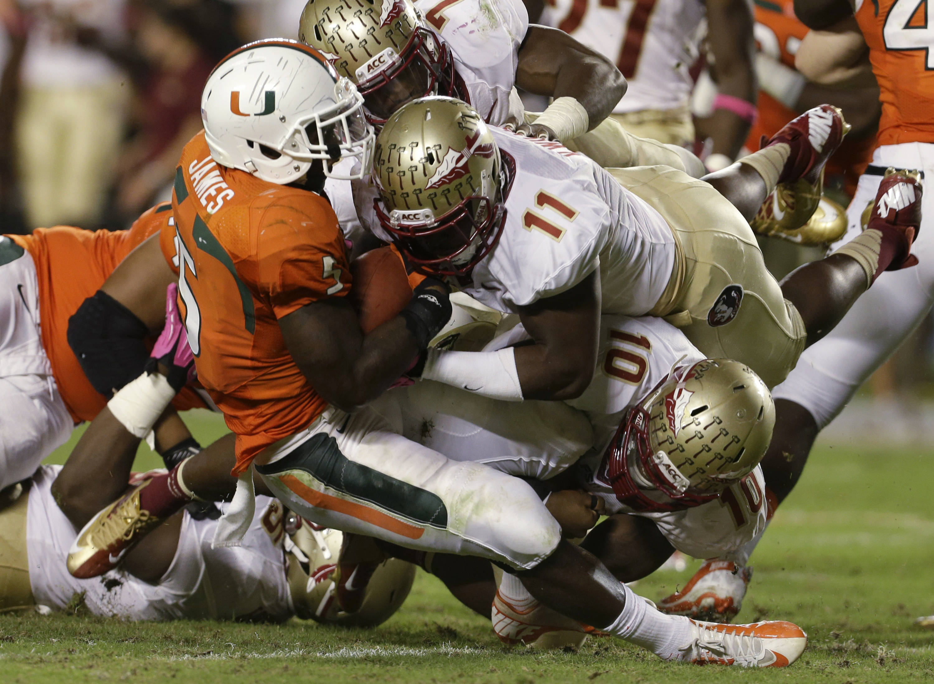 Miami running back Mike James (5) is tackled by Florida State linebackers Vince Williams (11) and Nick Moody (10) during the second half of an NCAA college football game Saturday, Oct. 20, 2012, in Miami. (AP Photo/Lynne Sladky)
