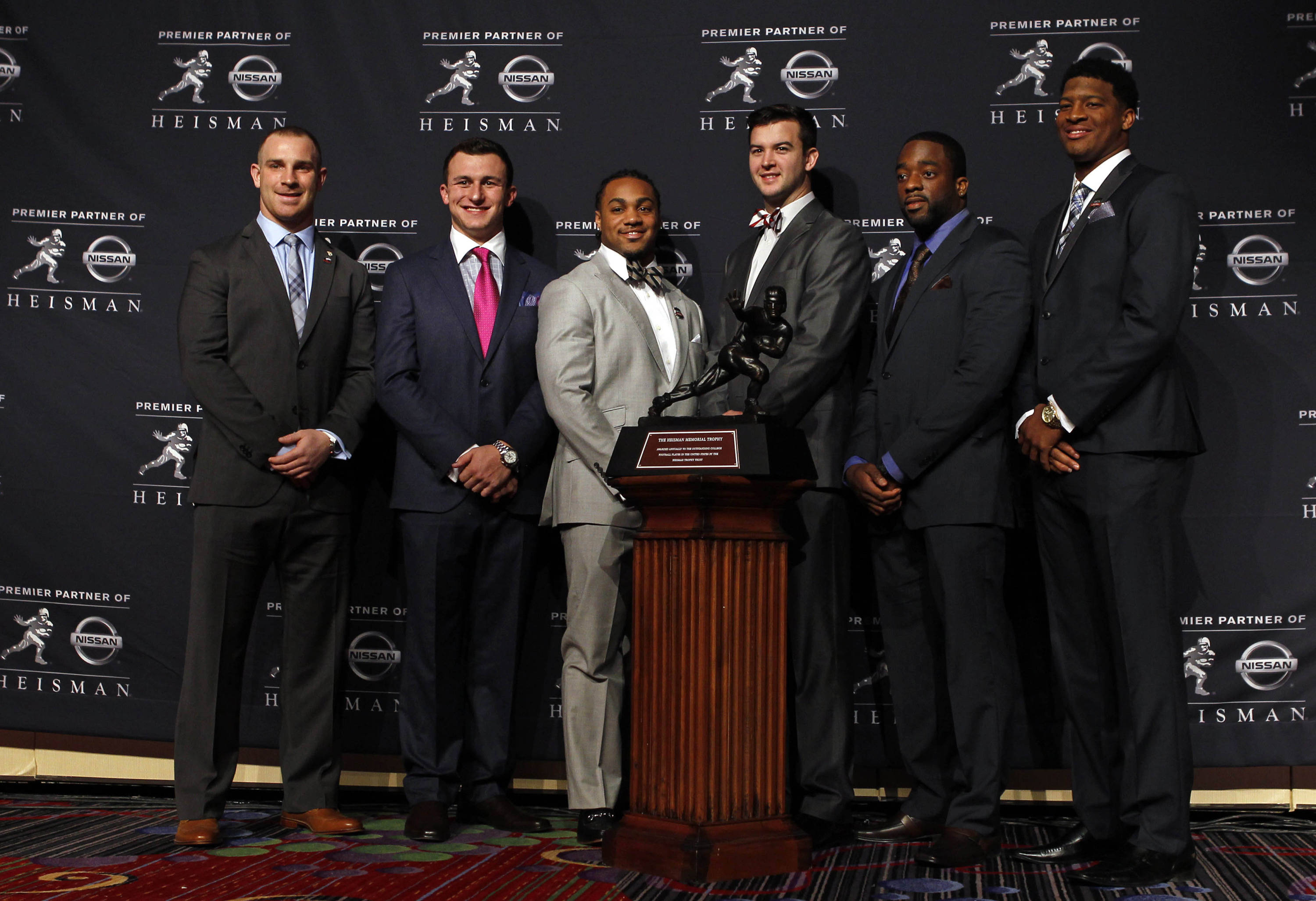 Dec 14, 2013; New York, NY, USA; (From left to right) Northern Illinois Huskies quarterback Jordan Lynch, and Texas A&M Aggies quarterback Johnny Manziel, and Auburn Tigers running back Tre Mason, and Alabama Crimson Tide quarterback AJ McCarron, and Boston College Eagles running back Andre Williams and Seminoles quarterback Jameis Winston pose for a photo with the Heisman Trophy during a press conference before the announcement of the 2013 Heisman Trophy winner at the Marriott Marquis in New Yo