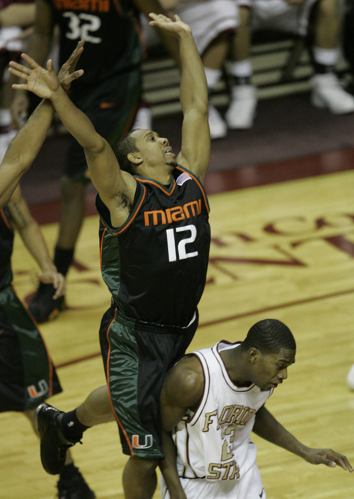 Miami's Anthony Harris (12) jumps on the back of Florida State's Toney Douglas after making a pass in the first half of a college basketball game, Saturday, Jan. 20, 2007, in Tallahassee, Fla. (AP Photo/Phil Coale)