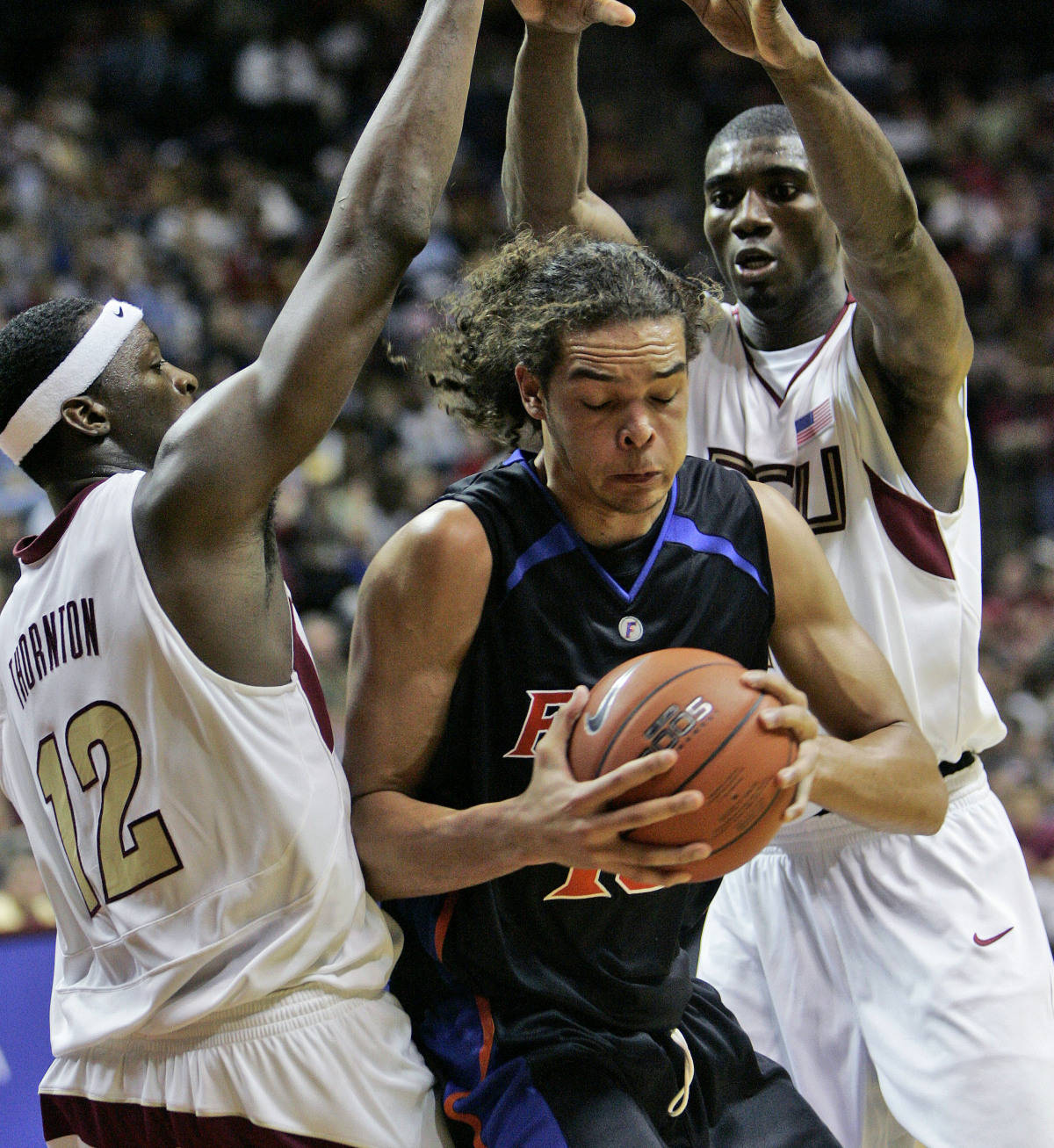 Florida's Joakim Noah, center, is surrounded by Florida State's Al Thornton, left, and Uche Echefu during the second half of a college basketball game, Sunday, Dec. 3, 2006, in Tallahassee, Fla.(AP Photo/Phil Coale)