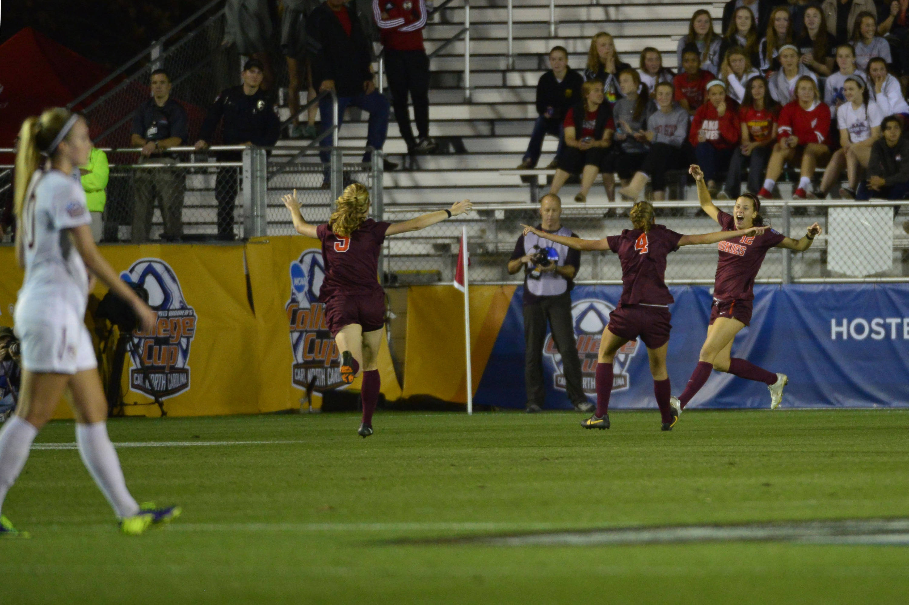 Dec 6, 2013; Cary, NC, USA; Virginia Tech Hokies forward Ashley Manning (12) celebrates with midfielder Kelsey Loupee (9) and forward Shannon Mayrose (4) after scoring a goal as Florida State Seminoles forward Berglind Thorvaldsdottir (10) is in the foreground in the first half at WakeMed Soccer Park. Mandatory Credit: Bob Donnan-USA TODAY Sports