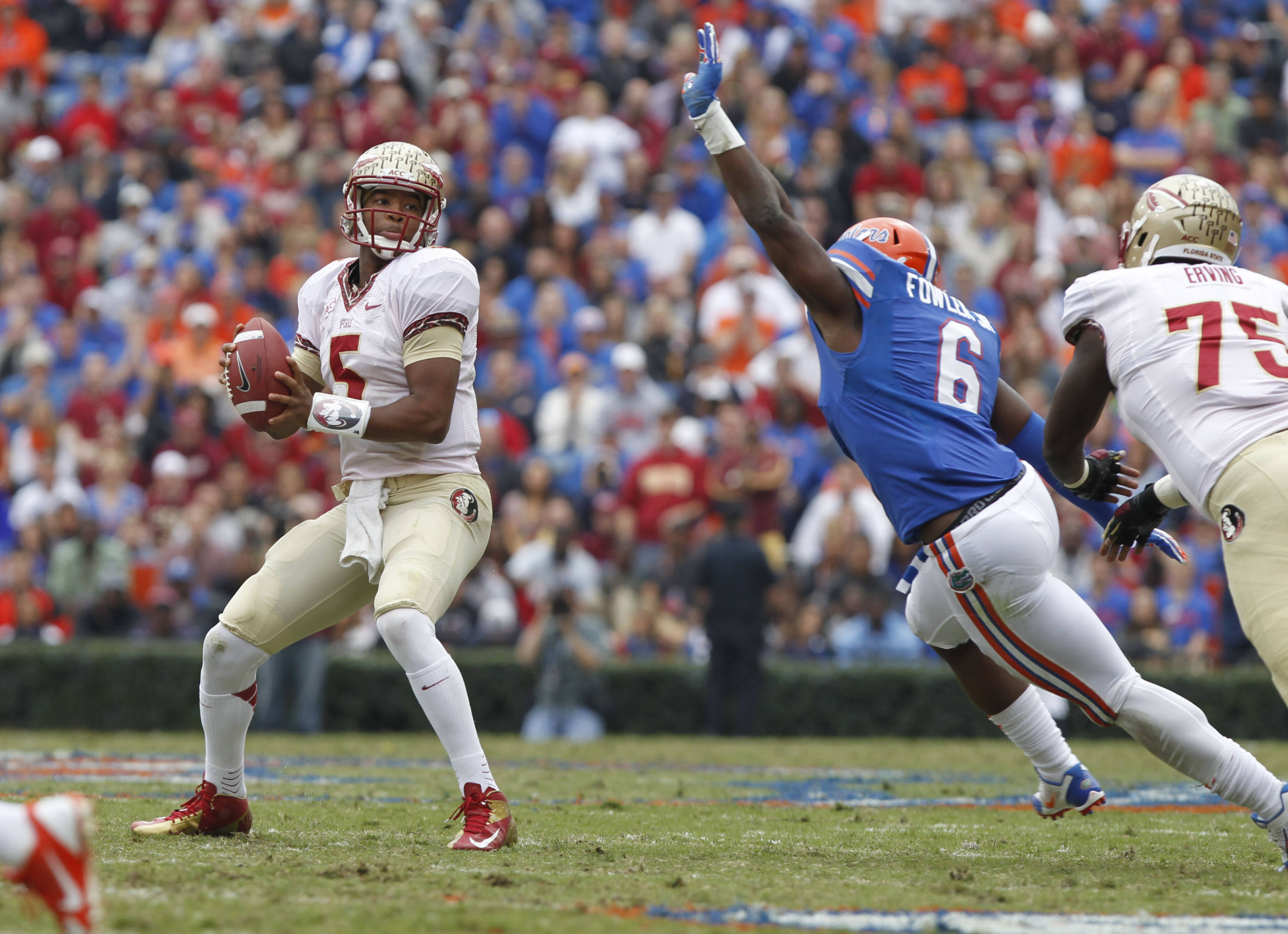 Jameis Winston (5) drops back as Florida Gators defensive end Dante Fowler Jr. (6) defends. Mandatory Credit: Kim Klement-USA TODAY Sports