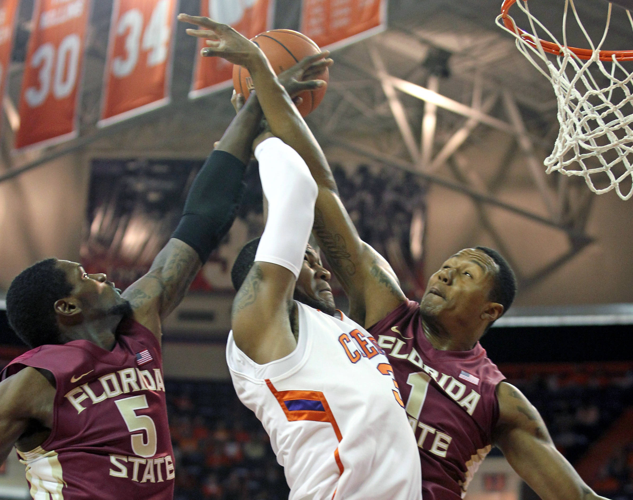 Clemson's Devin Booker, center, drives to the basket between Florida State's Bernard James, left, and Xavier Gibson during the first half of an NCAA college basketball game on Saturday. (AP Photo/Anderson Independent-Mail, Mark Crammer)