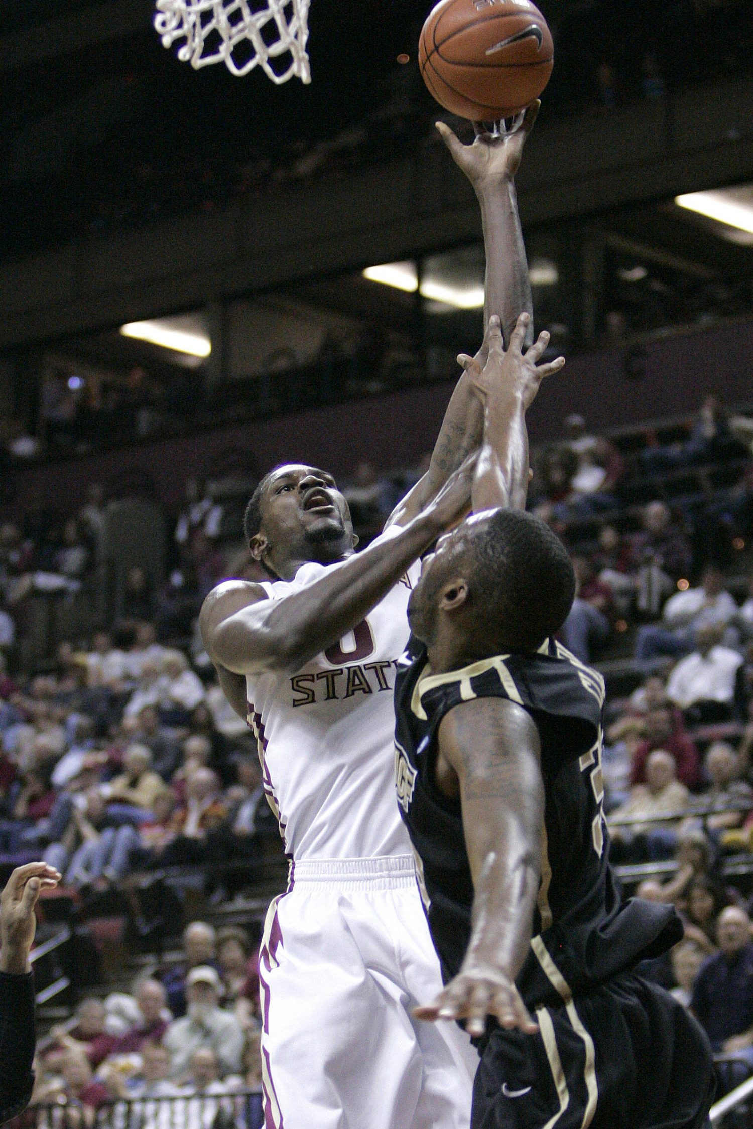 Florida State's Benard James scores over the defense of  Central Florida's Keith Clanton in the first half of an NCAA college basketball game which Florida State won 73-50 on Monday, Nov. 14, 2011, in Tallahassee, Fla.(AP Photo/Steve Cannon)