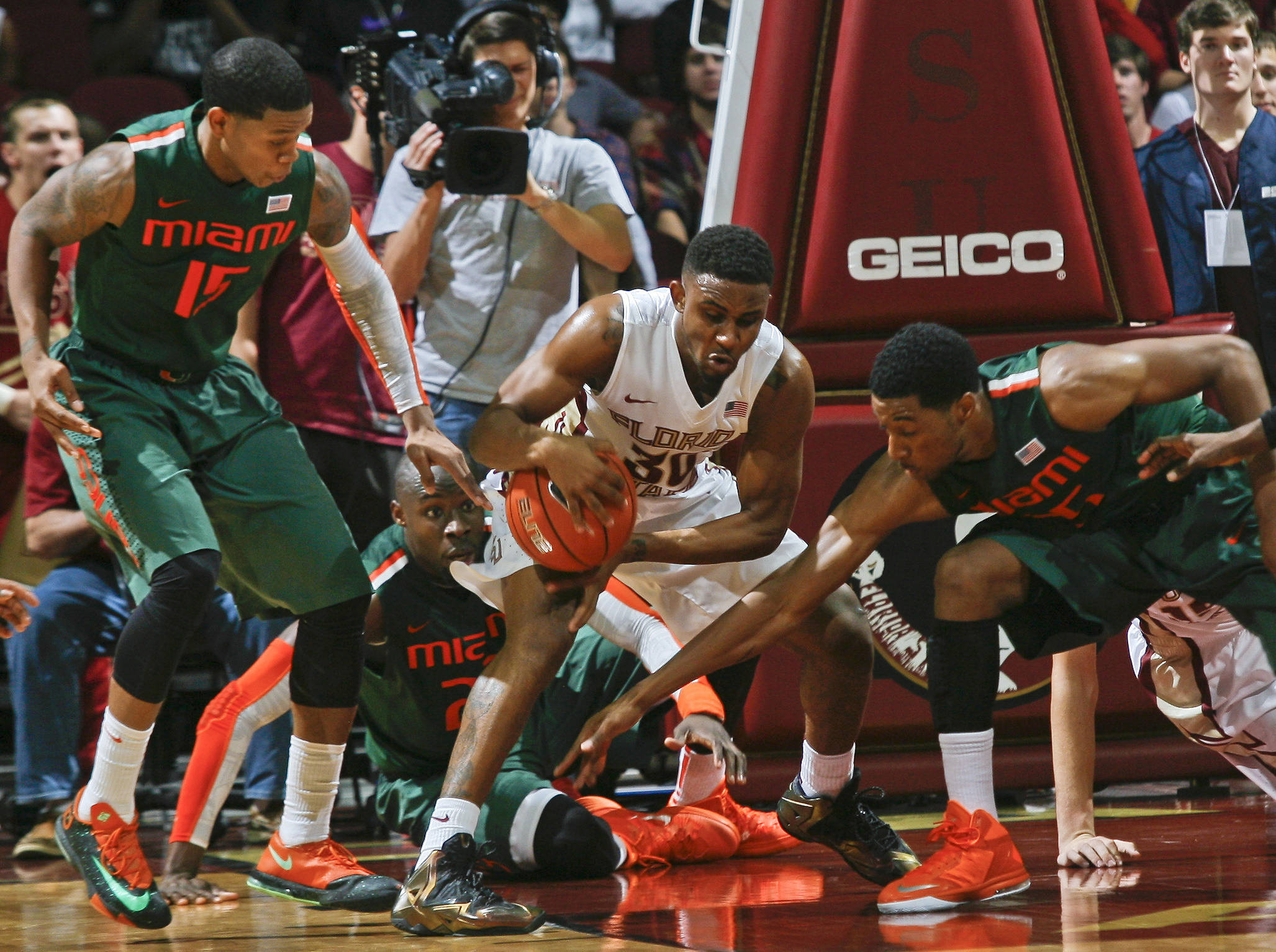 Feb 10, 2014; Tallahassee, FL, USA; Seminoles guard Ian Miller (30) is surrounded by Miami Hurricanes guard Rion Brown (15) and center Tonye Jekiri (in back) and guard Garrius Adams (25) in the second half. Phil Sears-USA TODAY Sports