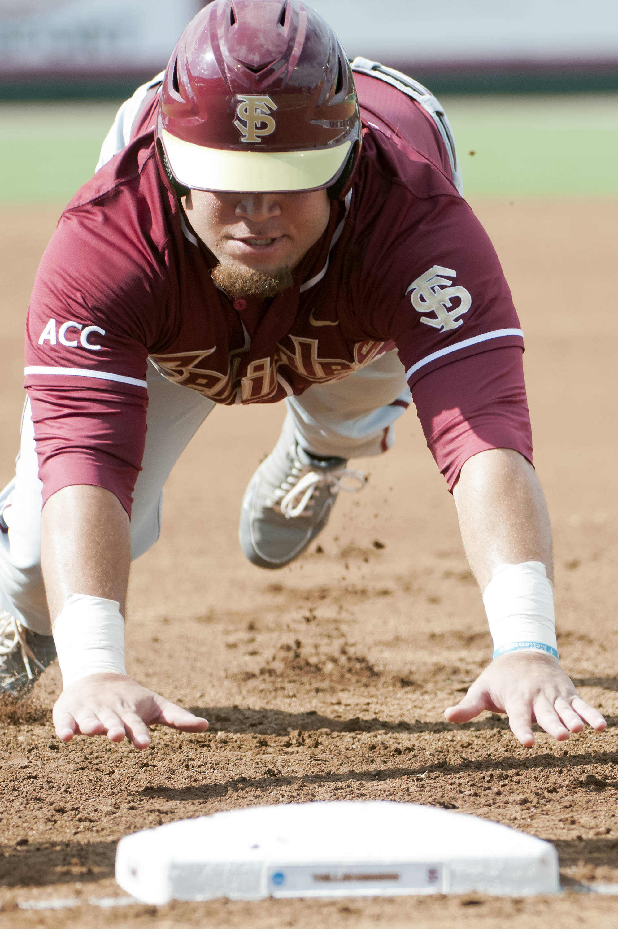 DJ Stewart (8) dives back to first base to avoid a pick off