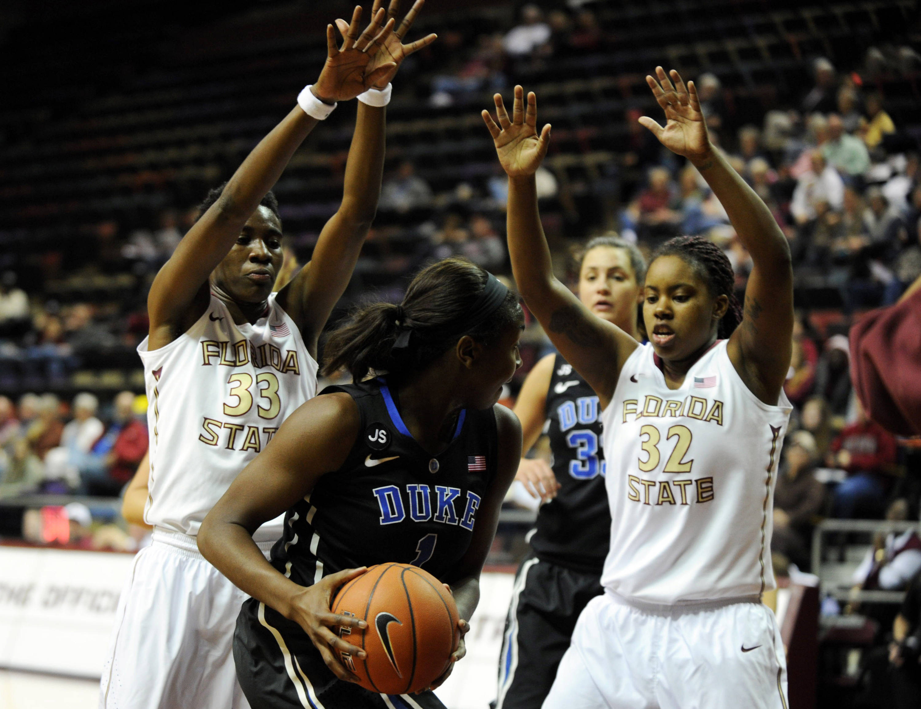 Jan 23, 2014; Tallahassee, FL, USA; Duke Blue Devils center Elizabeth Williams (1) tries to shoot past Florida State Seminoles forward Lauren Coleman (32) and forward Natasha Howard (33) during the first half of the game at the Donald L. Tucker Center (Tallahassee). Mandatory Credit: Melina Vastola-USA TODAY Sports