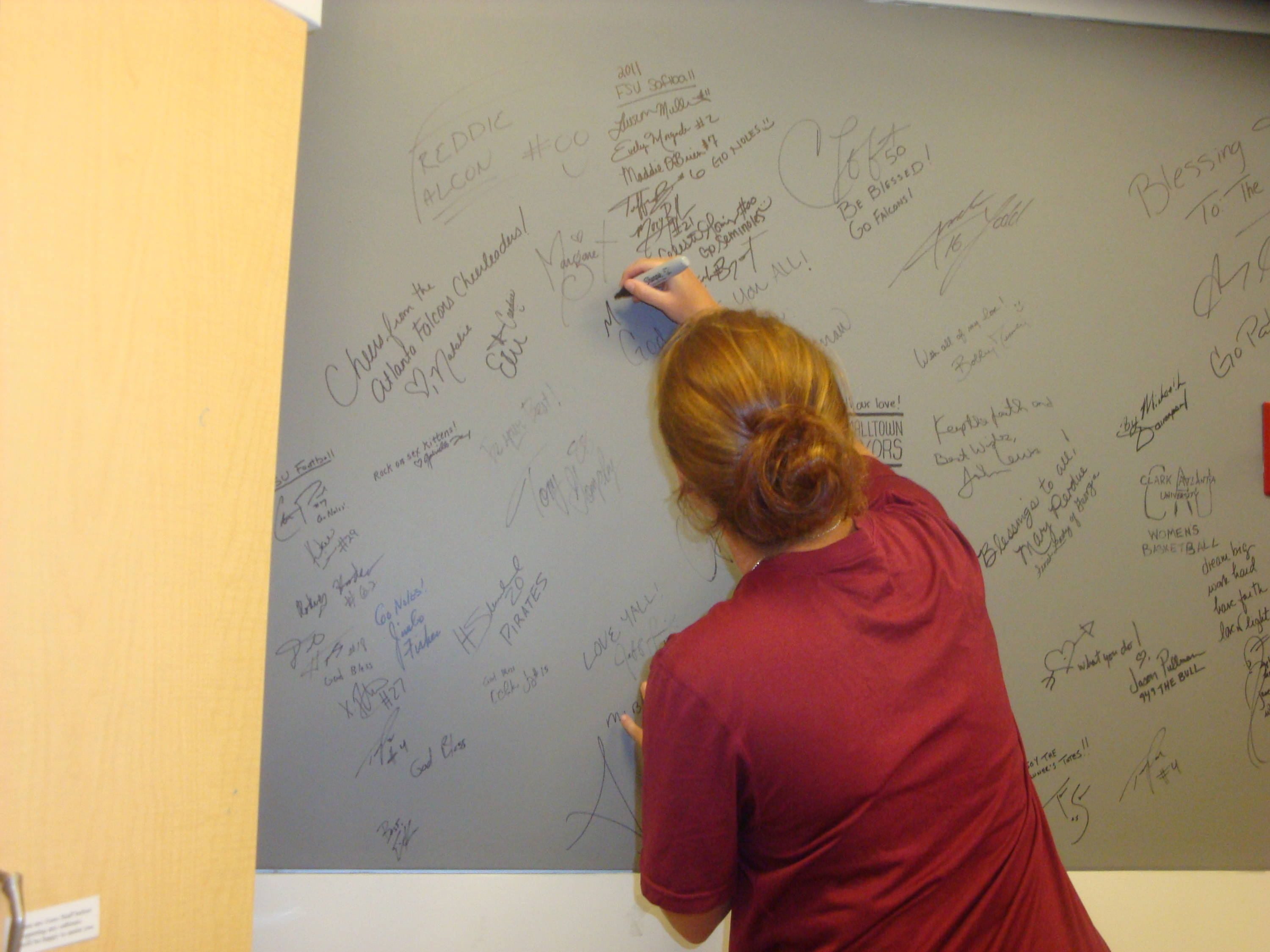 Mallory Borden adds her name to the signature wall