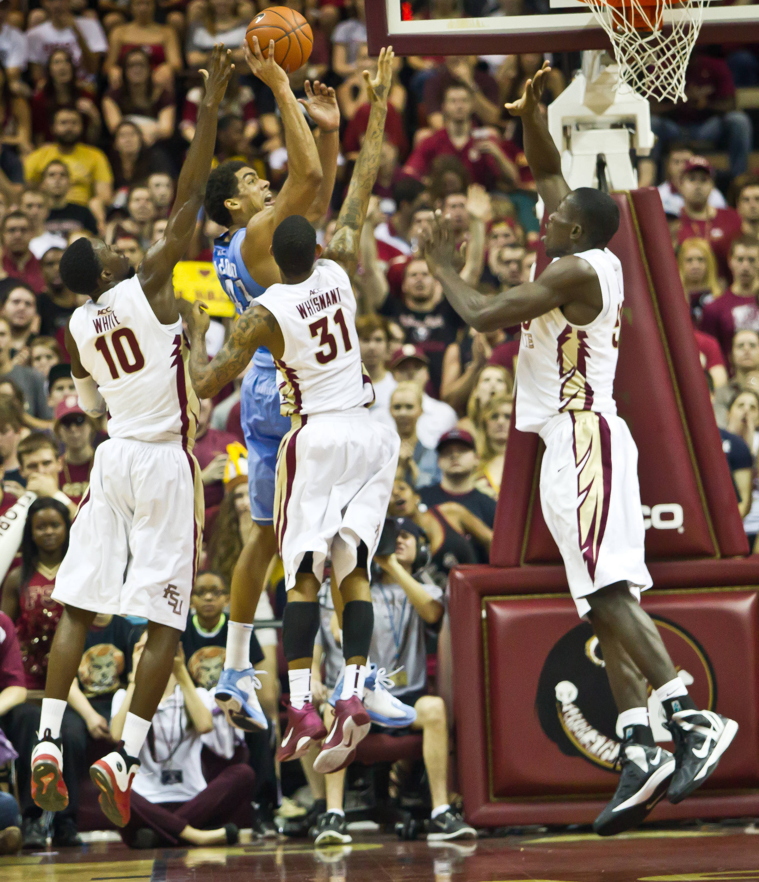 Okaro White (10), Whisnant Terry (31) & the FSU defense work again UNC's James McAdoo.