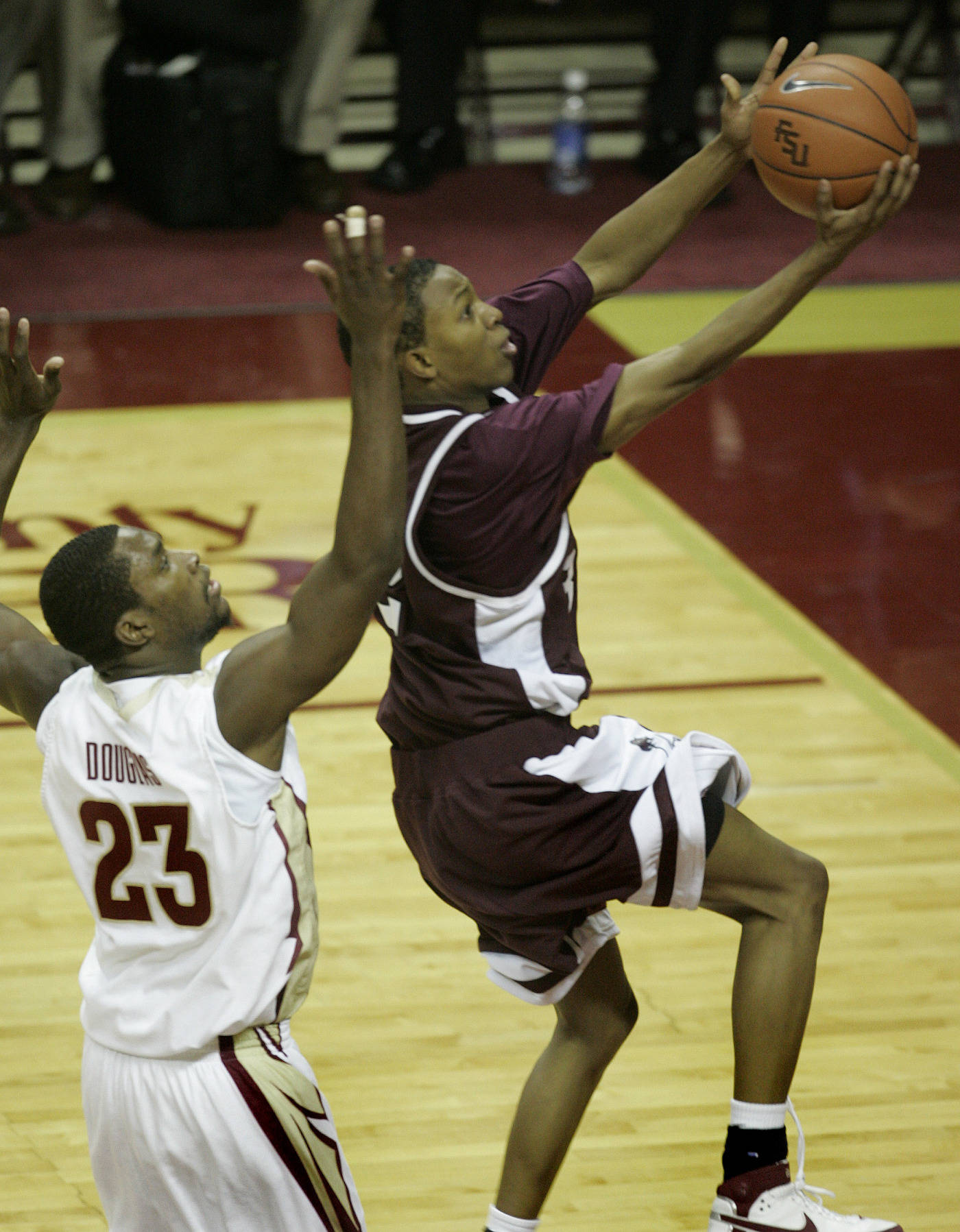 College of Charleston's Tony White, Jr. attempts to drive past Toney Douglas for two first-half points. (AP Photo/Phil Coale)