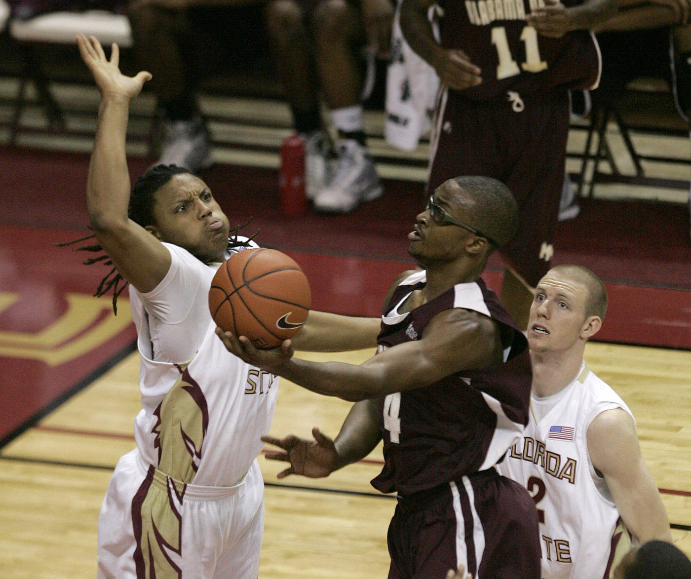Alabama A&M's Casey Cantey tries an underhand layup against the defense of Florida State's Terrance Shannon, left, and Jordan DeMercy, right, during the second half of an NCAA college basketball game on Thursday, Dec. 31, 2009, in Tallahassee, Fla. Florida State won 81-34. (AP Photo/Steve Cannon)