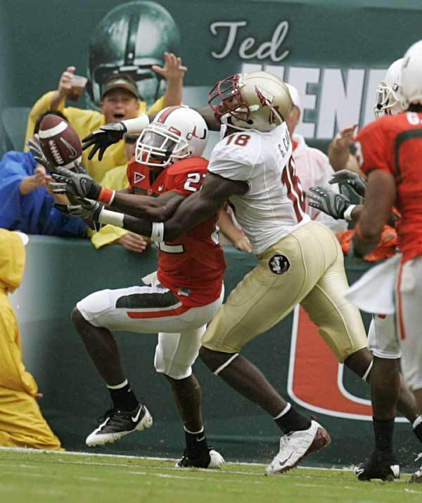 Miami defensive back Bruce Johnson (22) intercepts a Florida State pass as FSU wide receiver Greg Carr (18) tackles Johnson during the first quarter.