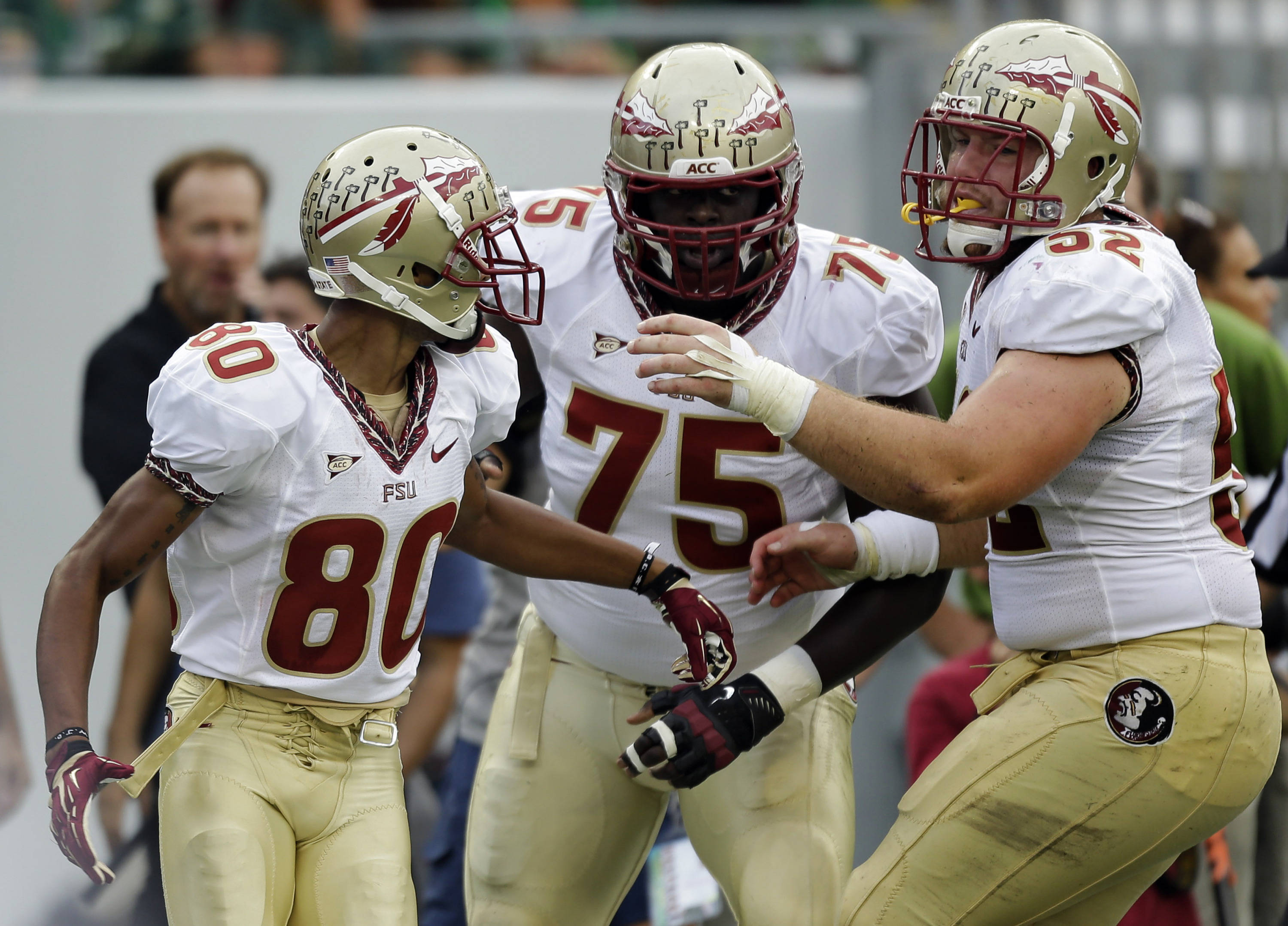 Florida State wide receiver Rashad Greene (80) celebrates with teammates Cameron Erving (75) and  Bryan Stork (52) after scoring a touchdown against South Florida during the first quarter. (AP Photo/Chris O'Meara)