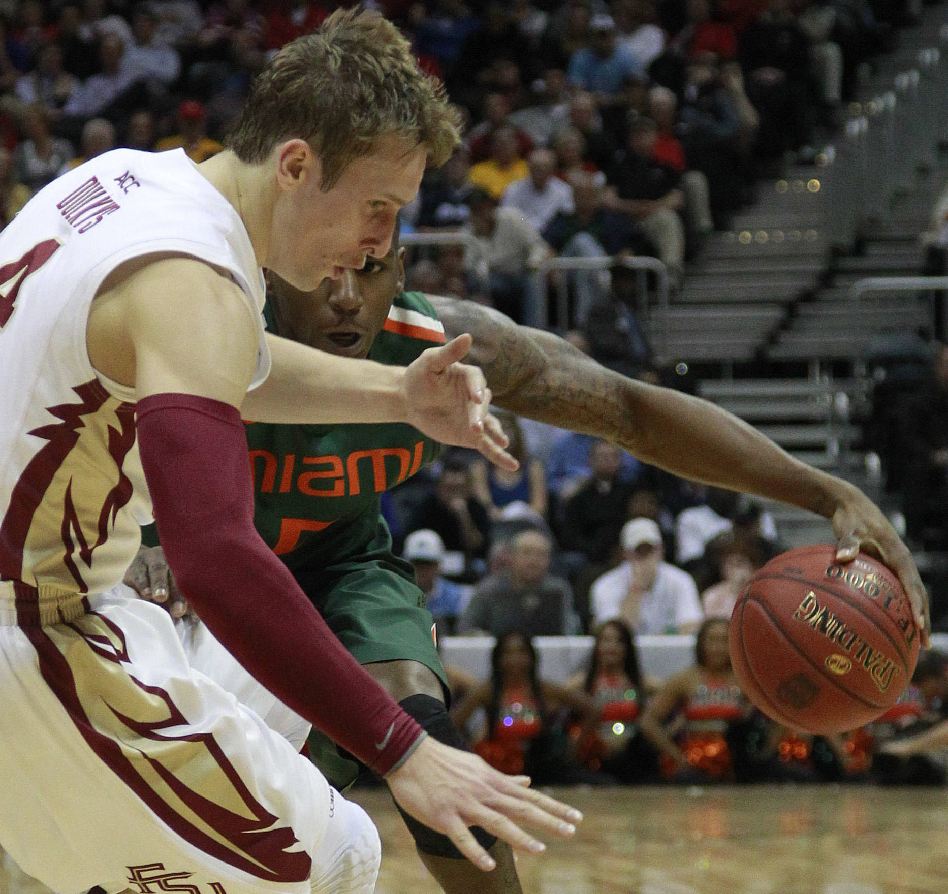 Miami guard/forward DeQuan Jones (5) works the ball against Florida State guard Deividas Dulkys (4) during the first half of an NCAA college basketball game in the quarterfinals of the Atlantic Coast Conference tournament, Friday, March 9, 2012, in Atlanta. (AP Photo/John Bazemore)