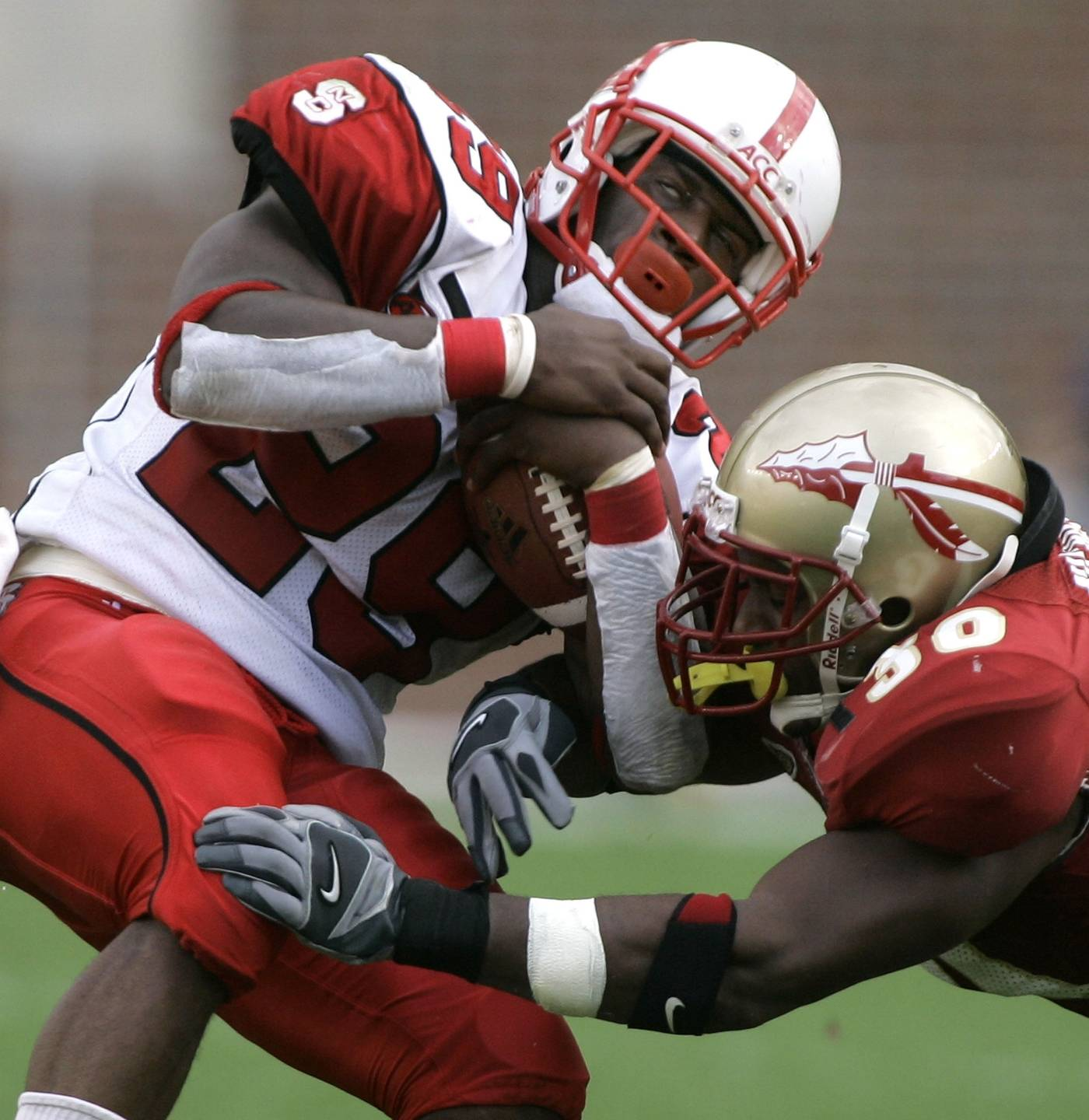 North Carolina State running back Jamelle Eugene, left, is tackled by Florida State's Derek Nicholson during the third quarter. (AP Photo/Phil Coale)