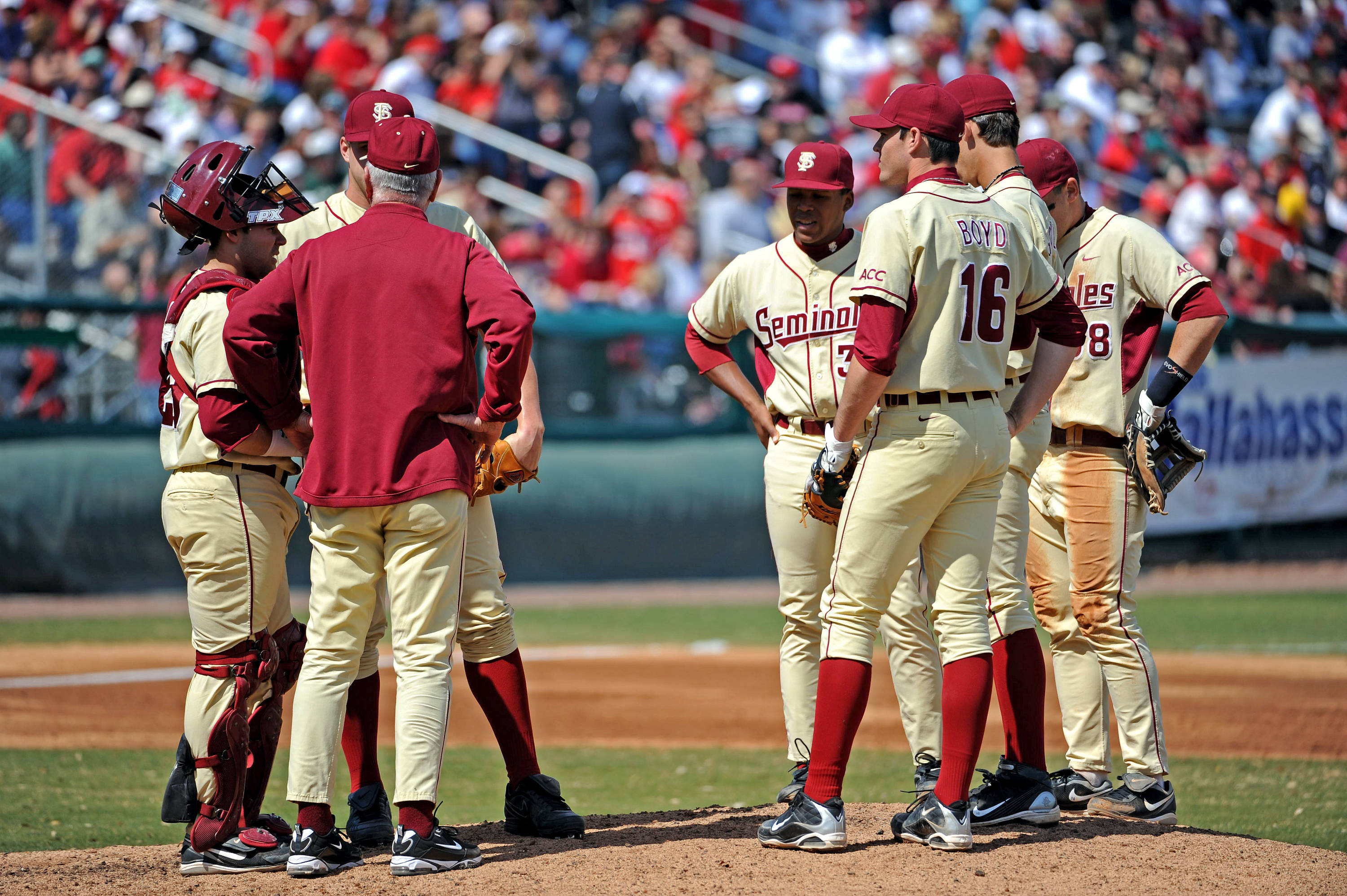 Head coach Mike Martin meets with the Seminoles at the mound.