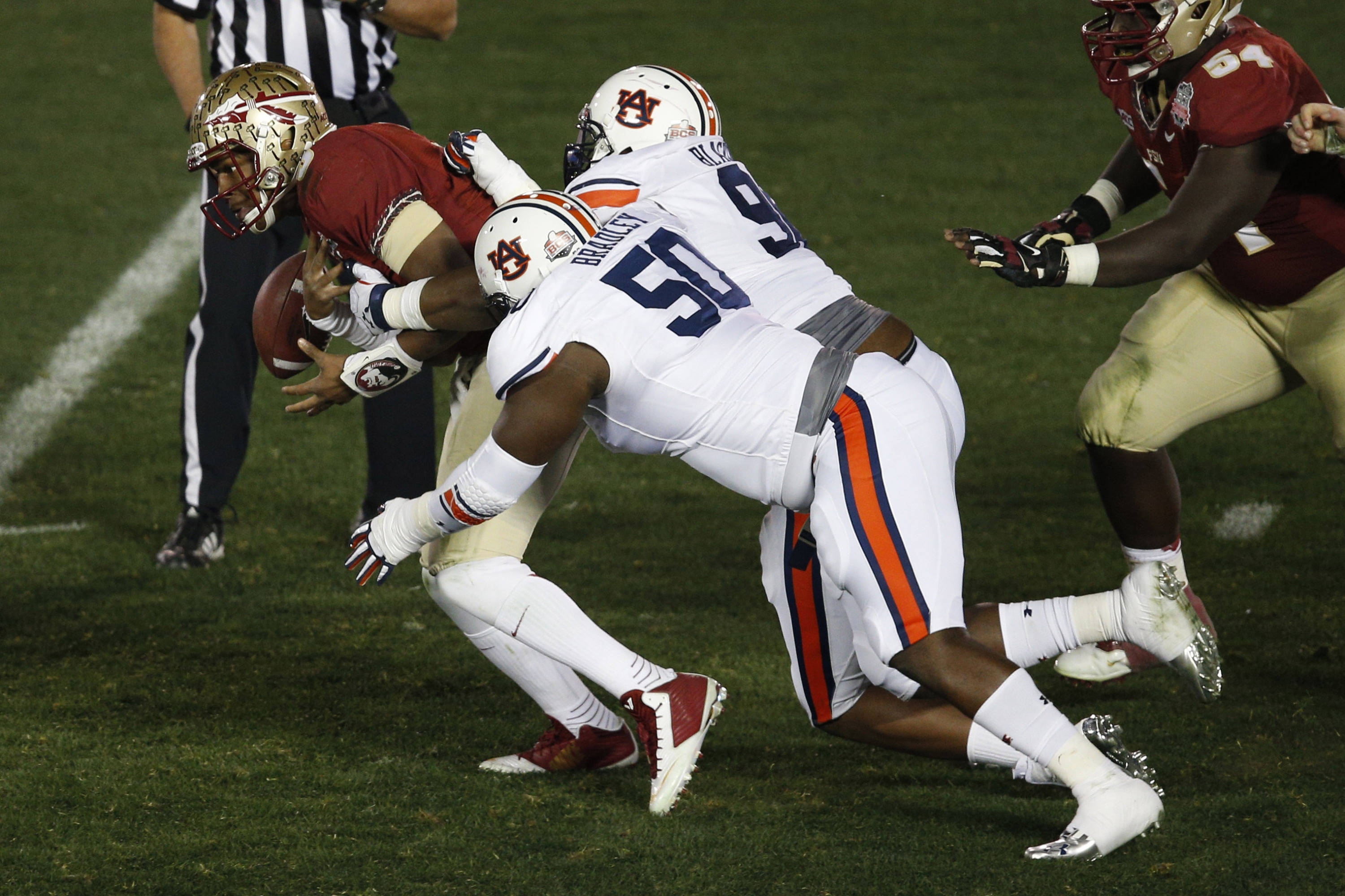 Jan 6, 2014; Pasadena, CA, USA; Auburn Tigers defensive tackle Ben Bradley (50) and defensive lineman Angelo Blackson (98) tackle Florida State Seminoles quarterback Jameis Winston (5) causing a fumble during the first half of the 2014 BCS National Championship game at the Rose Bowl.  Mandatory Credit: Kelvin Kuo-USA TODAY Sports