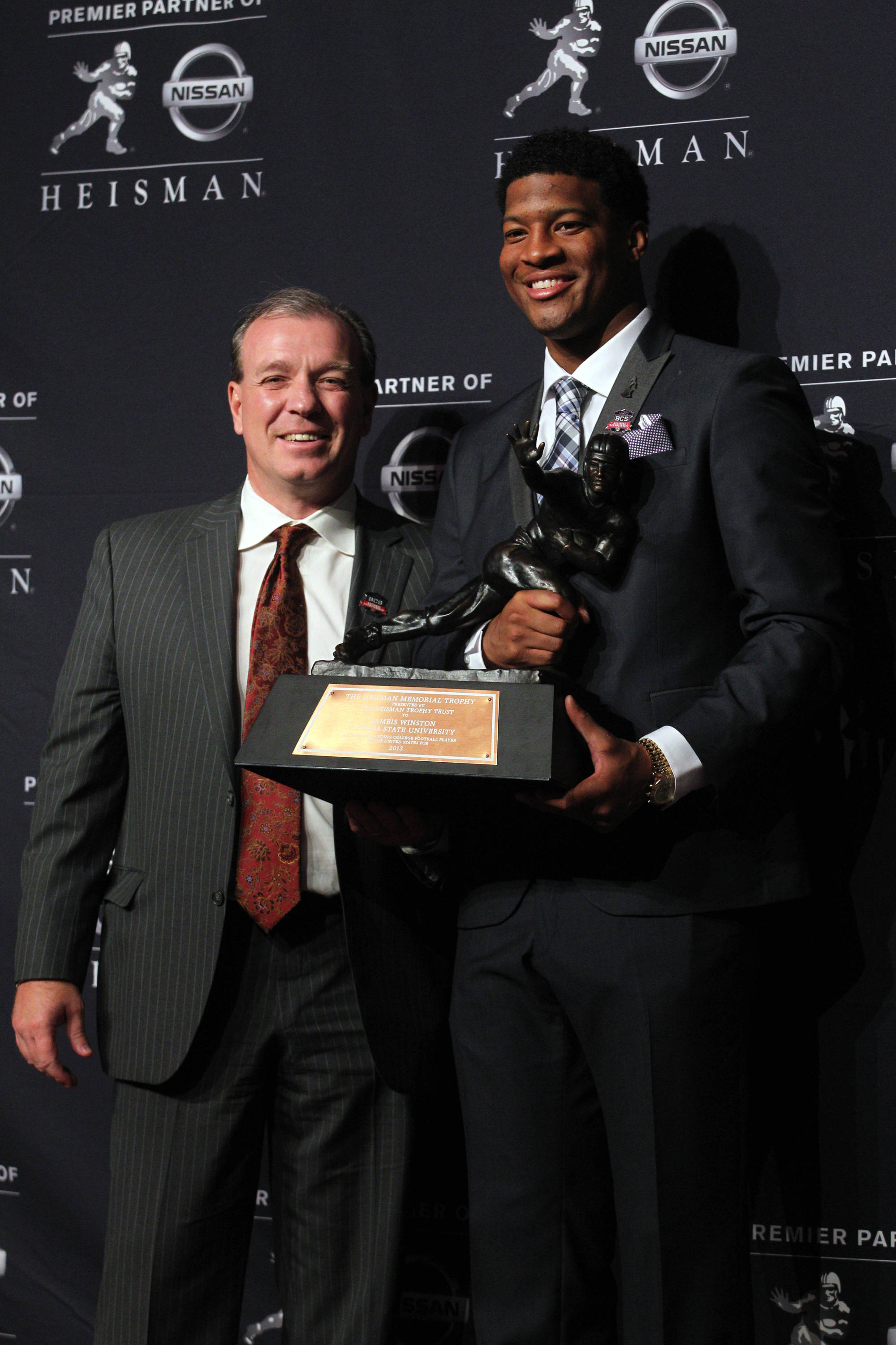Dec 14, 2013; New York, NY, USA; Seminoles quarterback and 2013 Heisman Trophy winner Jameis Winston (right) and Seminoles head coach Jimbo Fisher pose with the trophy during a press conference. Brad Penner-USA TODAY Sports