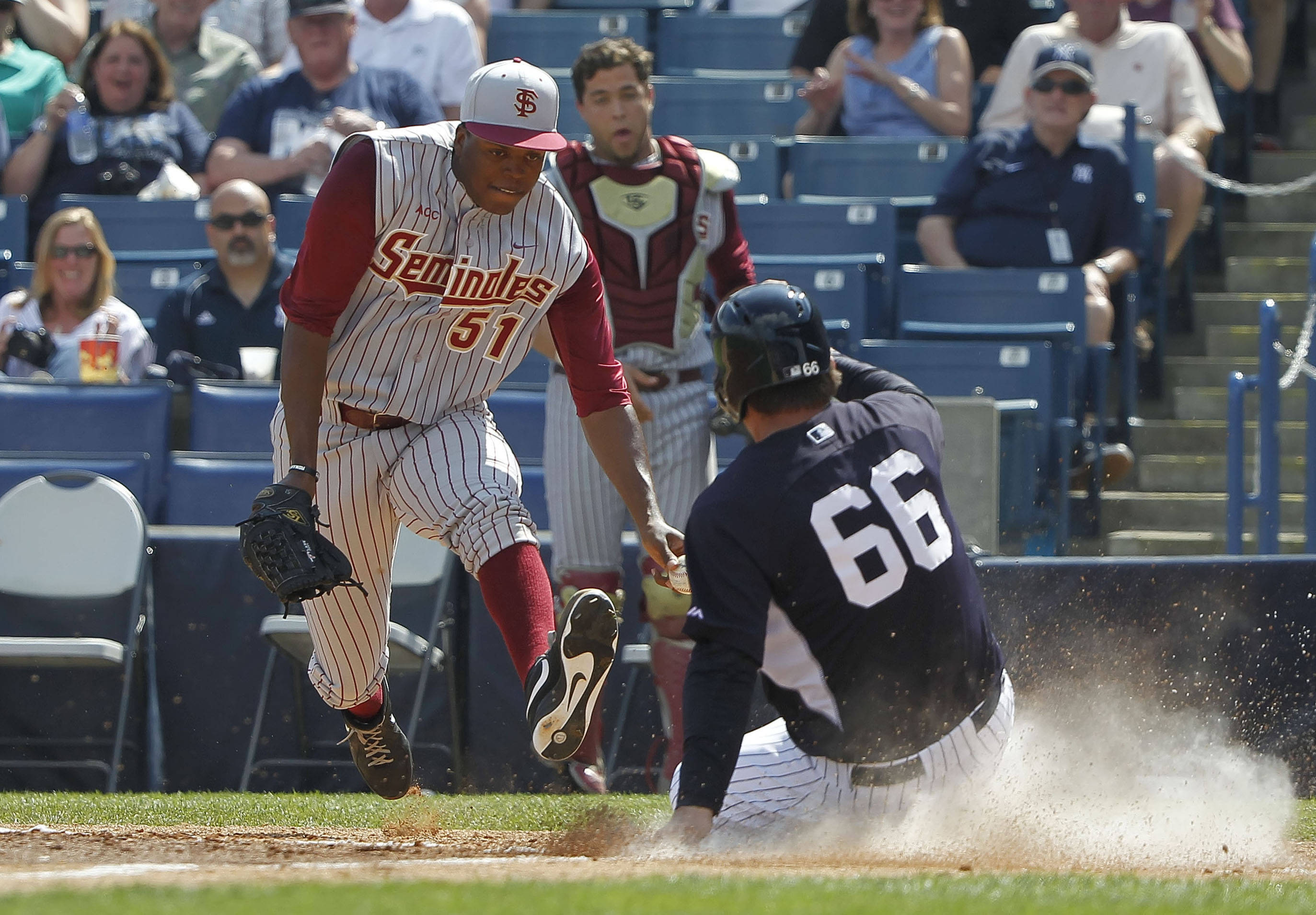 Feb 25, 2014; Tampa, FL, USA; Florida State Seminoles pitcher Brandon Johnson (51) attempted to tag out New York Yankees catcher John Ryan Murphy (66) as he scored during the third inning at George M. Steinbrenner Field. Mandatory Credit: Kim Klement-USA TODAY Sports