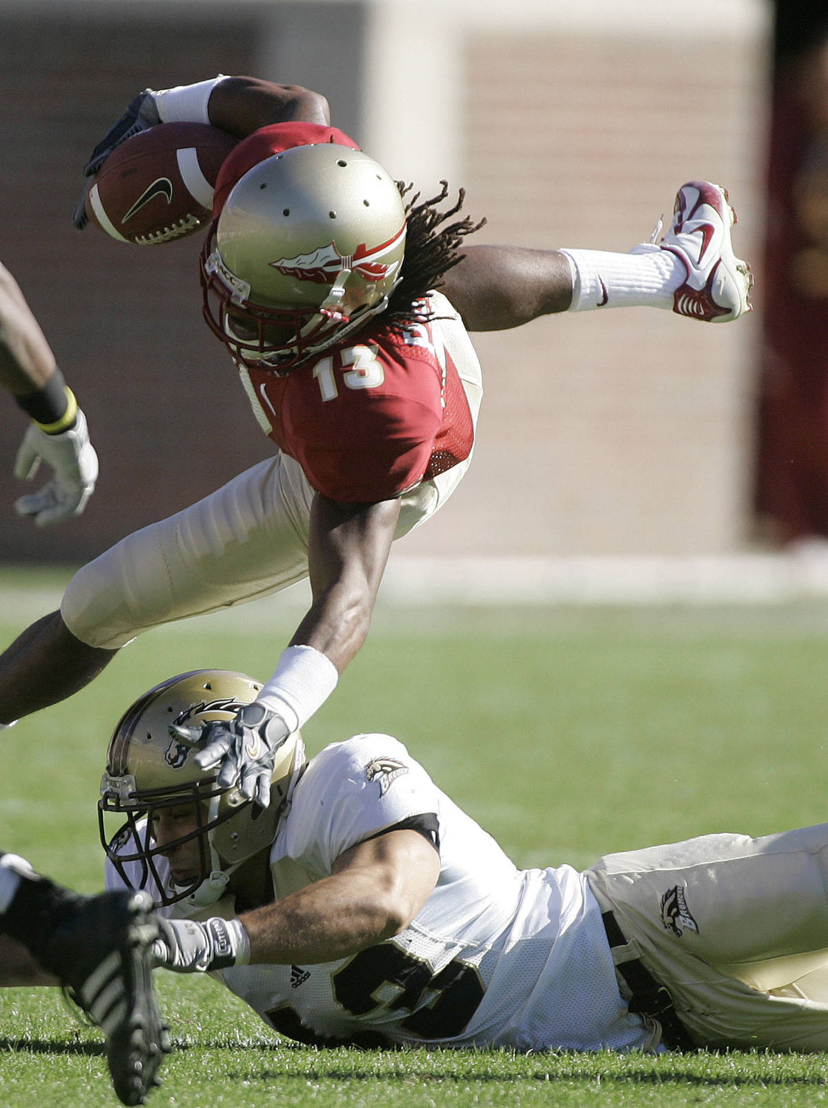 Florida State's Preston Parker, top, goes airborne as he is tackled by Western Michigan defender Ameer Ismail, bottom, during the first quarter of a football game, Saturday, Nov. 18, 2006, in Tallahassee, Fla. (AP Photo/Phil Coale)