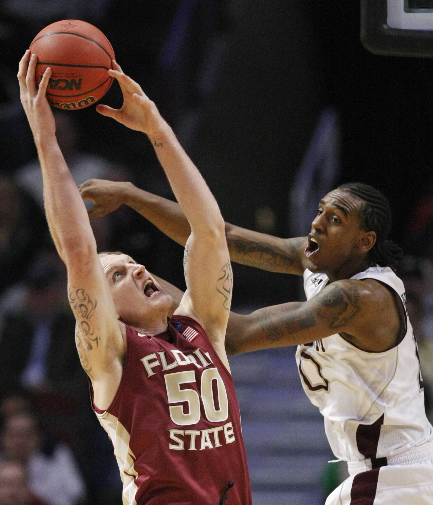 Florida State's Jon Kreft grabs a rebound in front of Texas A&M's David Loubeau in the first half . (AP Photo/Charles Rex Arbogast)