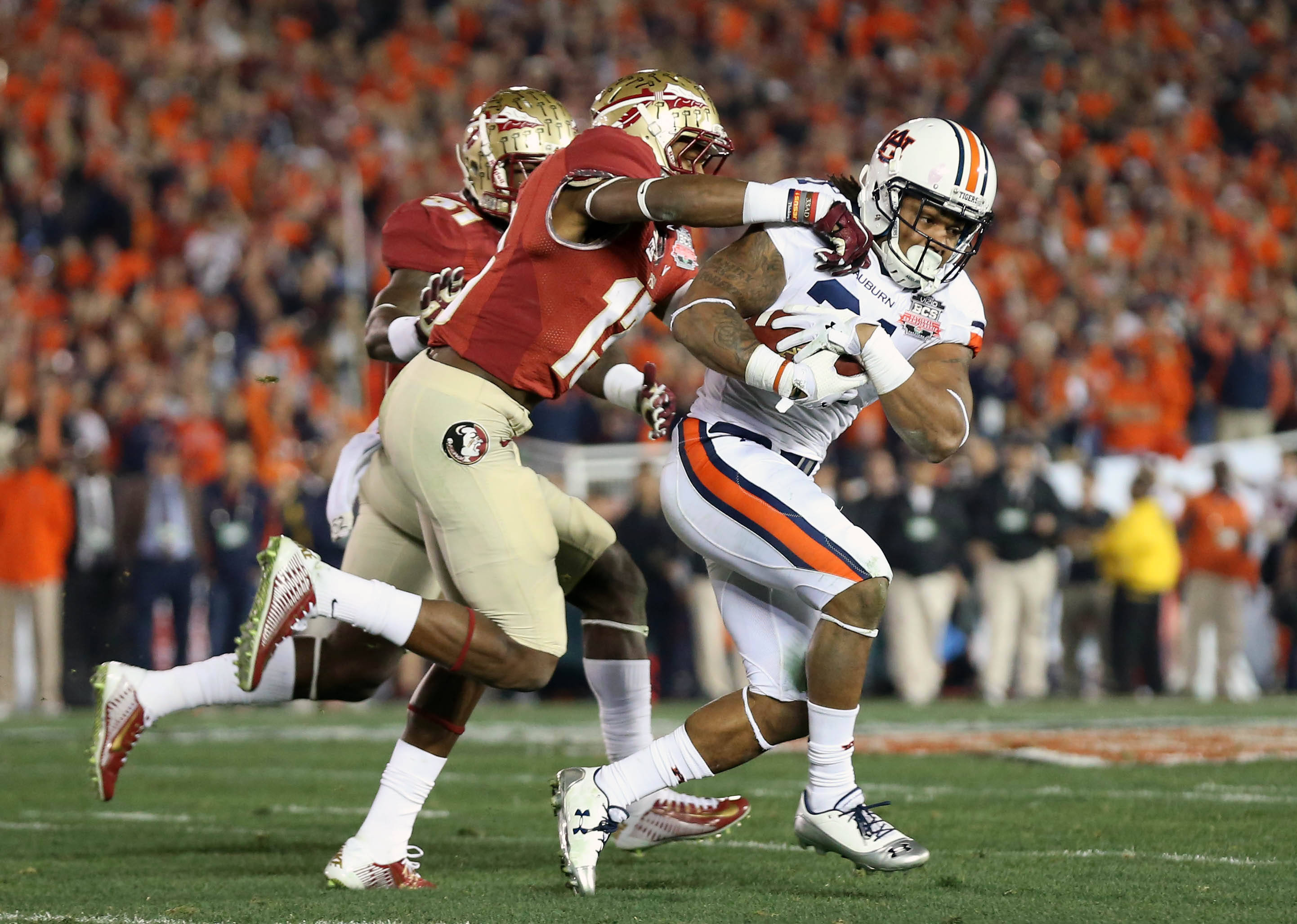 Jan 6, 2014; Pasadena, CA, USA; Auburn Tigers running back Tre Mason (21) carries the ball as he is tackled by Florida State Seminoles defensive back Jalen Ramsey (13) during the first half of the 2014 BCS National Championship game at the Rose Bowl.  Mandatory Credit: Matthew Emmons-USA TODAY Sports