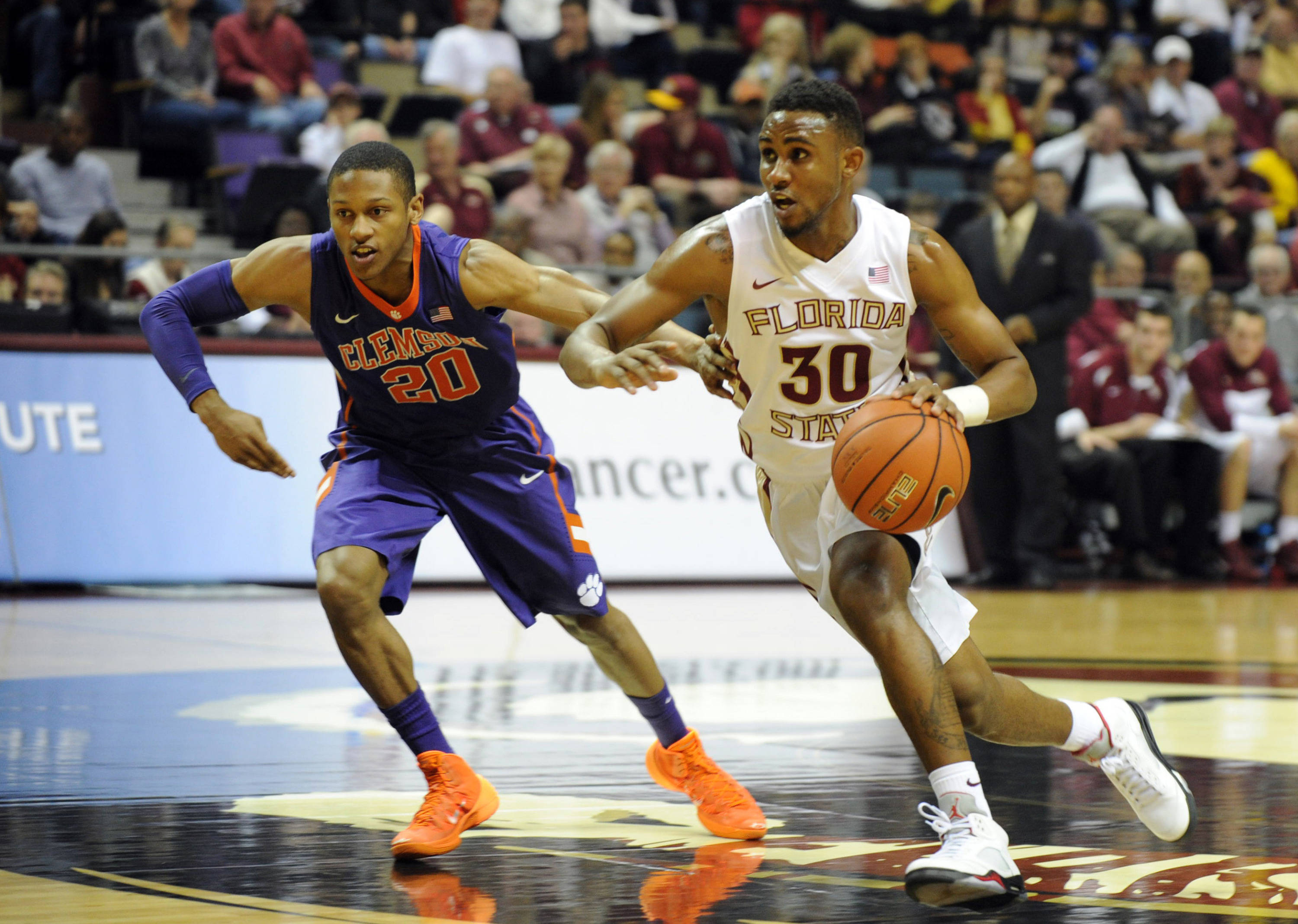 Feb 1, 2014; Tallahassee, FL, USA; Florida State Seminoles guard Ian Miller (30) moves the ball past Clemson Tigers guard Jordan Roper (20) during the first half at the Donald L. Tucker Center. Mandatory Credit: Melina Vastola-USA TODAY Sports