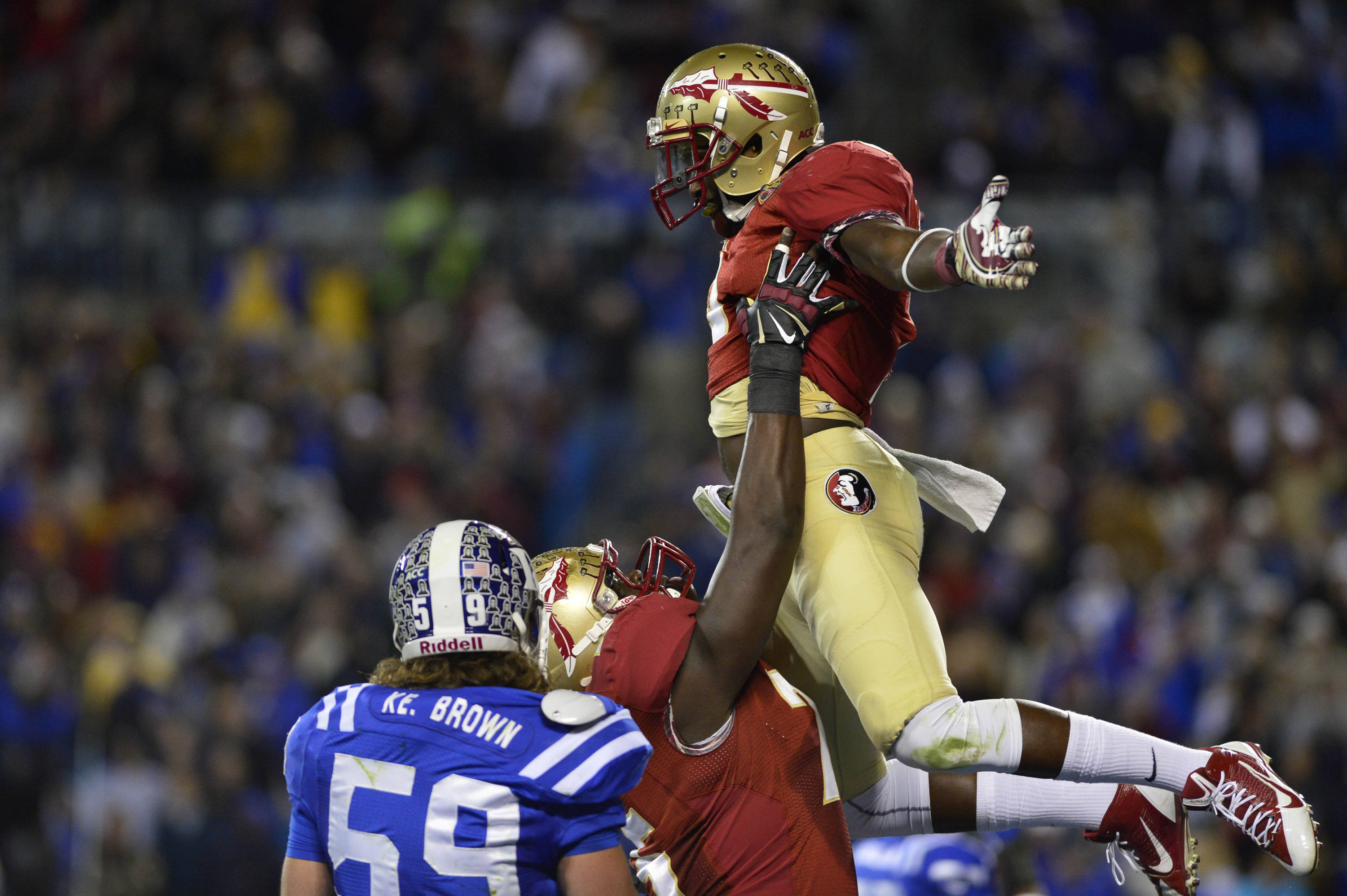 Dec 7, 2013; Charlotte, NC, USA; Florida State Seminoles running back Karlos Williams (9) is lifted into the air by offensive linesman Cameron Erving (75) after scoring a touchdown as Duke Blue Devils linebacker Kelby Brown (59) looks on in the second quarter at Bank of America Stadium. Mandatory Credit: Bob Donnan-USA TODAY Sports