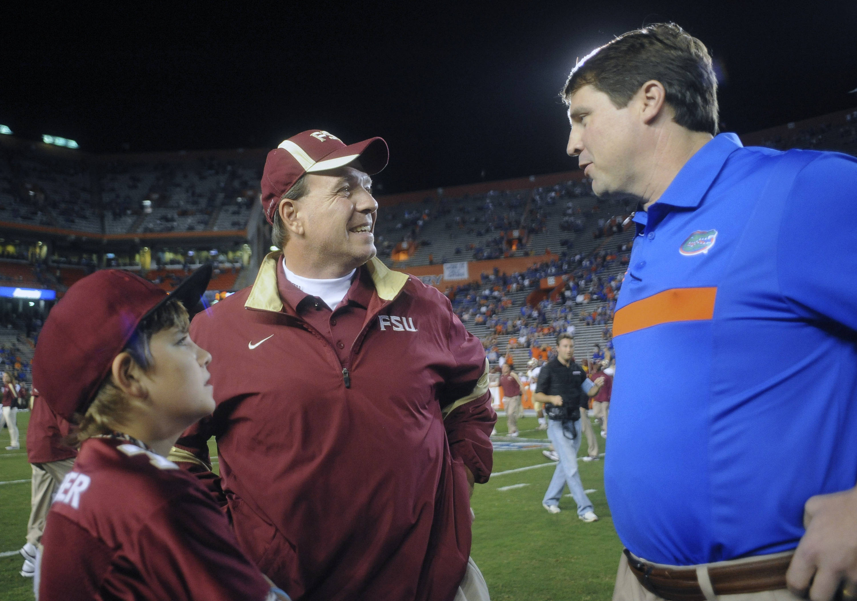 Florida head coach Will Muschamp, right, greets Florida State head coach Jimbo Fisher, center, and son Trey Fisher before an NCAA college football game on Saturday, Nov. 26, 2011, in Gainesville, Fla. (AP Photo/Phil Sandlin)