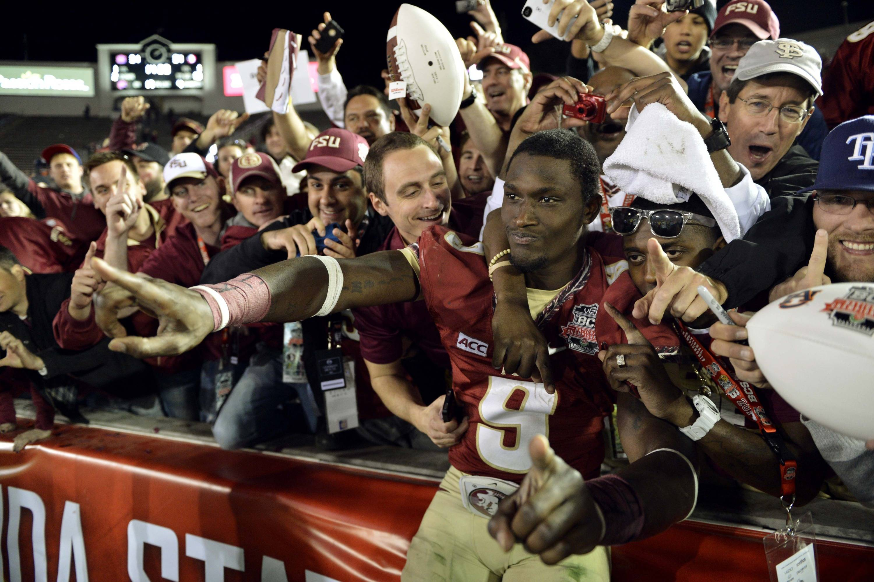 Jan 6, 2014; Pasadena, CA, USA; Florida State Seminoles running back Karlos Williams celebrates with fans in the stands after the 2014 BCS National Championship game against the Auburn Tigers at the Rose Bowl.  Mandatory Credit: Robert Hanashiro-USA TODAY Sports