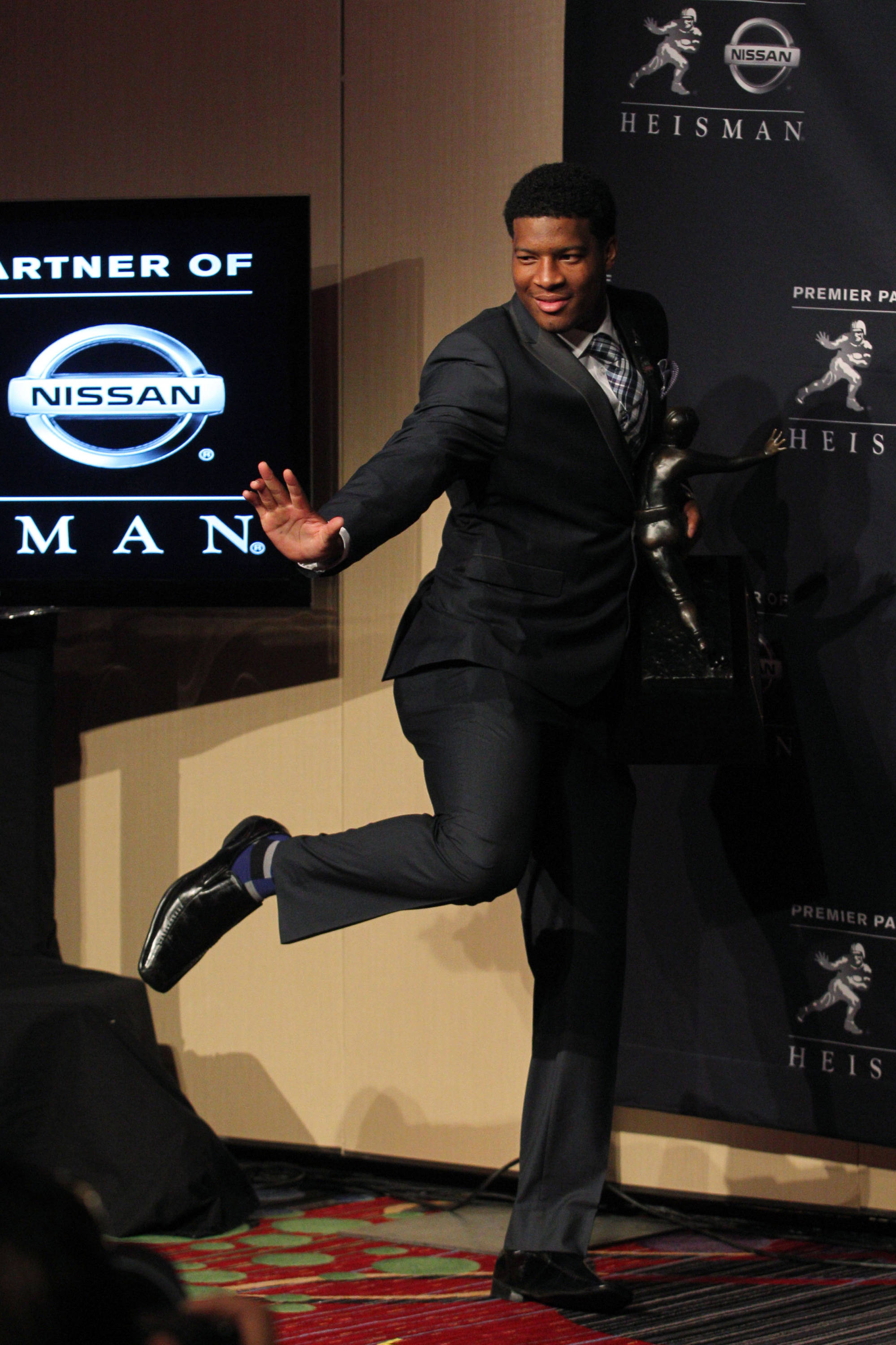 Dec 14, 2013; New York, NY, USA; Seminoles quarterback and 2013 Heisman Trophy winner Jameis Winston strikes a Heisman pose while holding the trophy during a press conference. Brad Penner-USA TODAY Sports