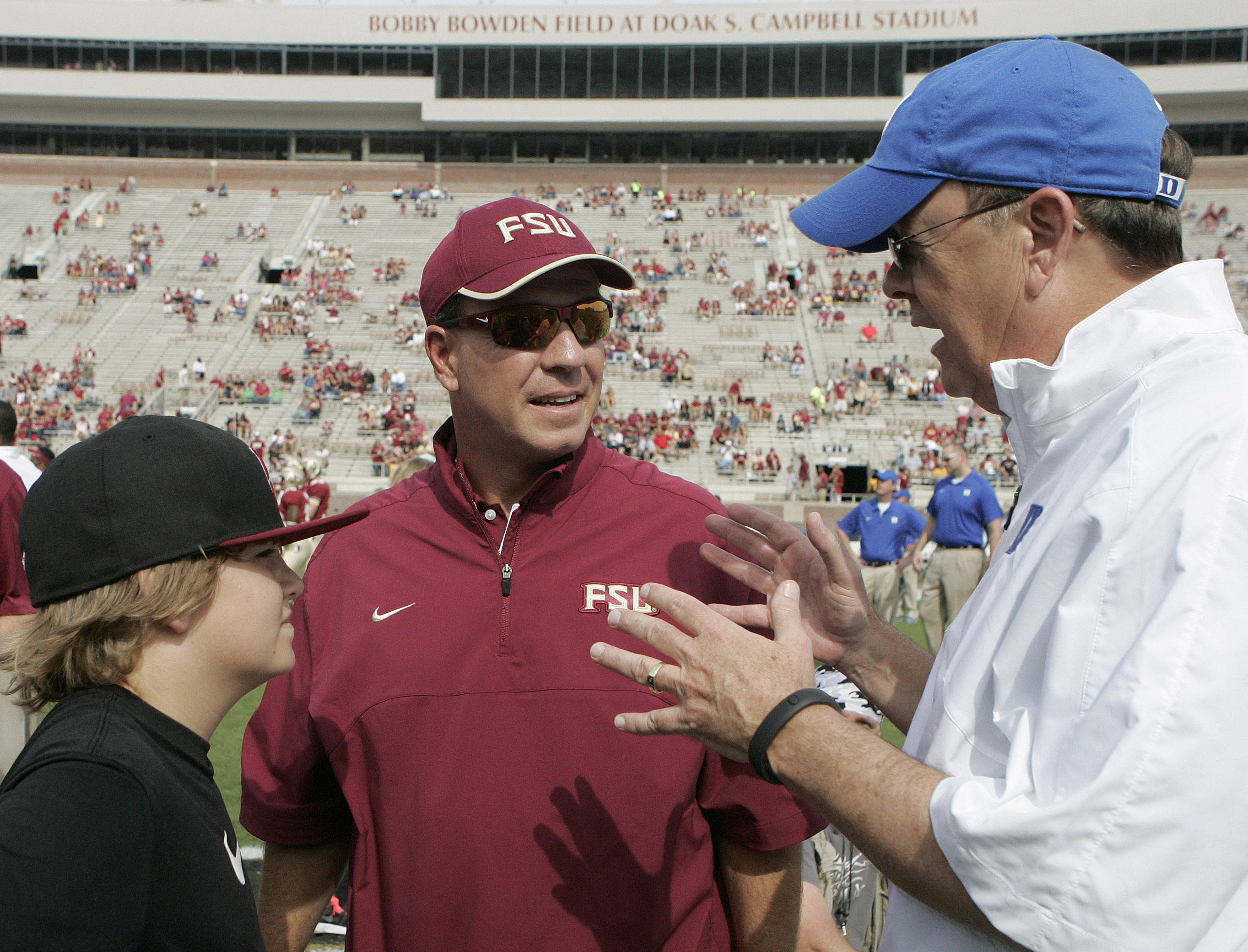 Duke head coach, David Cutcliffe, right, talks with Florida State head coach Jimbo Fisher and his son Trey Fisher before the start of the game. (AP Photo/Steve Cannon)