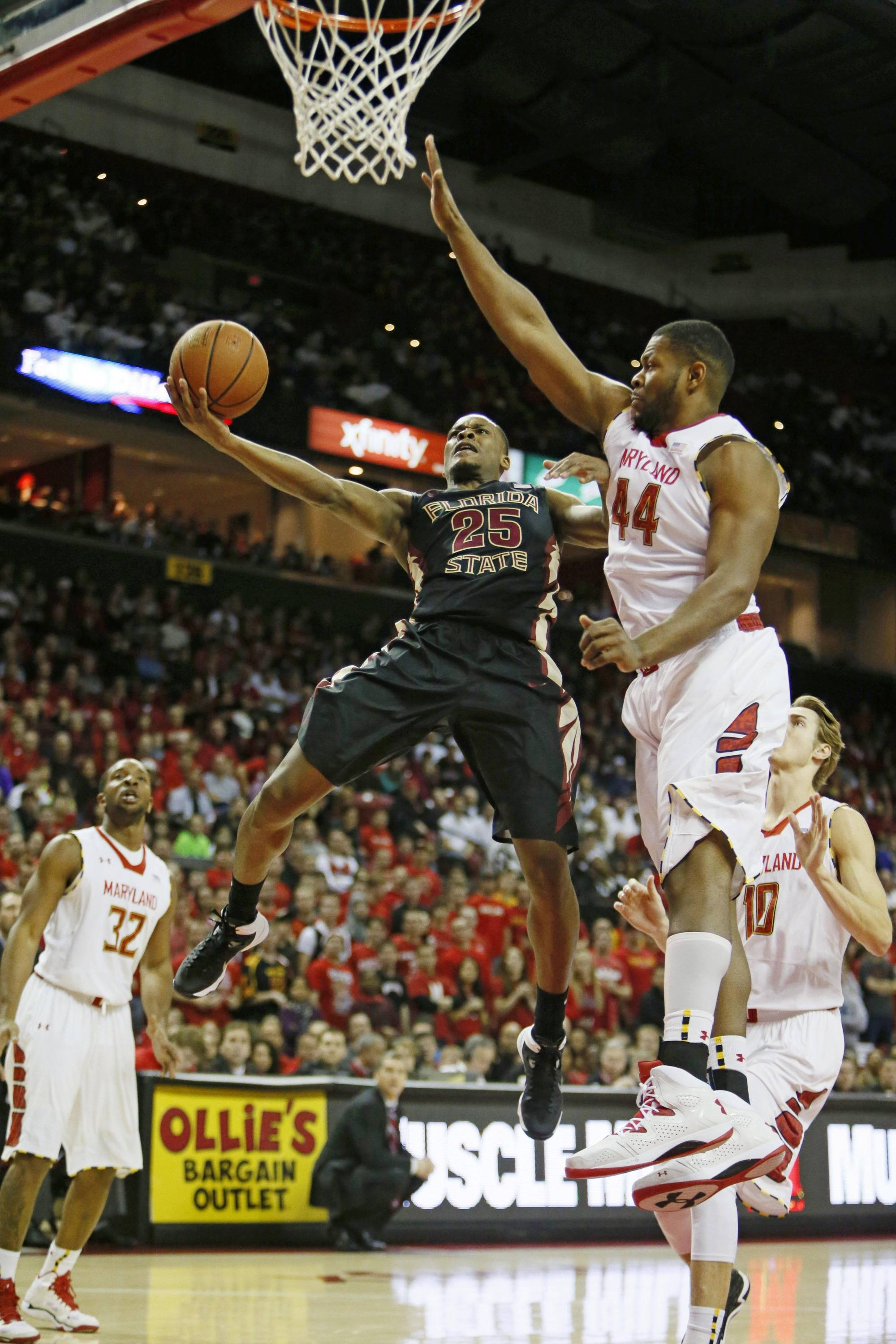 Feb 8, 2014; College Park, MD, USA; Florida State Seminoles forward Aaron Thomas (25) shoots while defended by Maryland Terrapins forward Shaquille Cleare (44) at Comcast Center. Mandatory Credit: Mitch Stringer-USA TODAY Sports