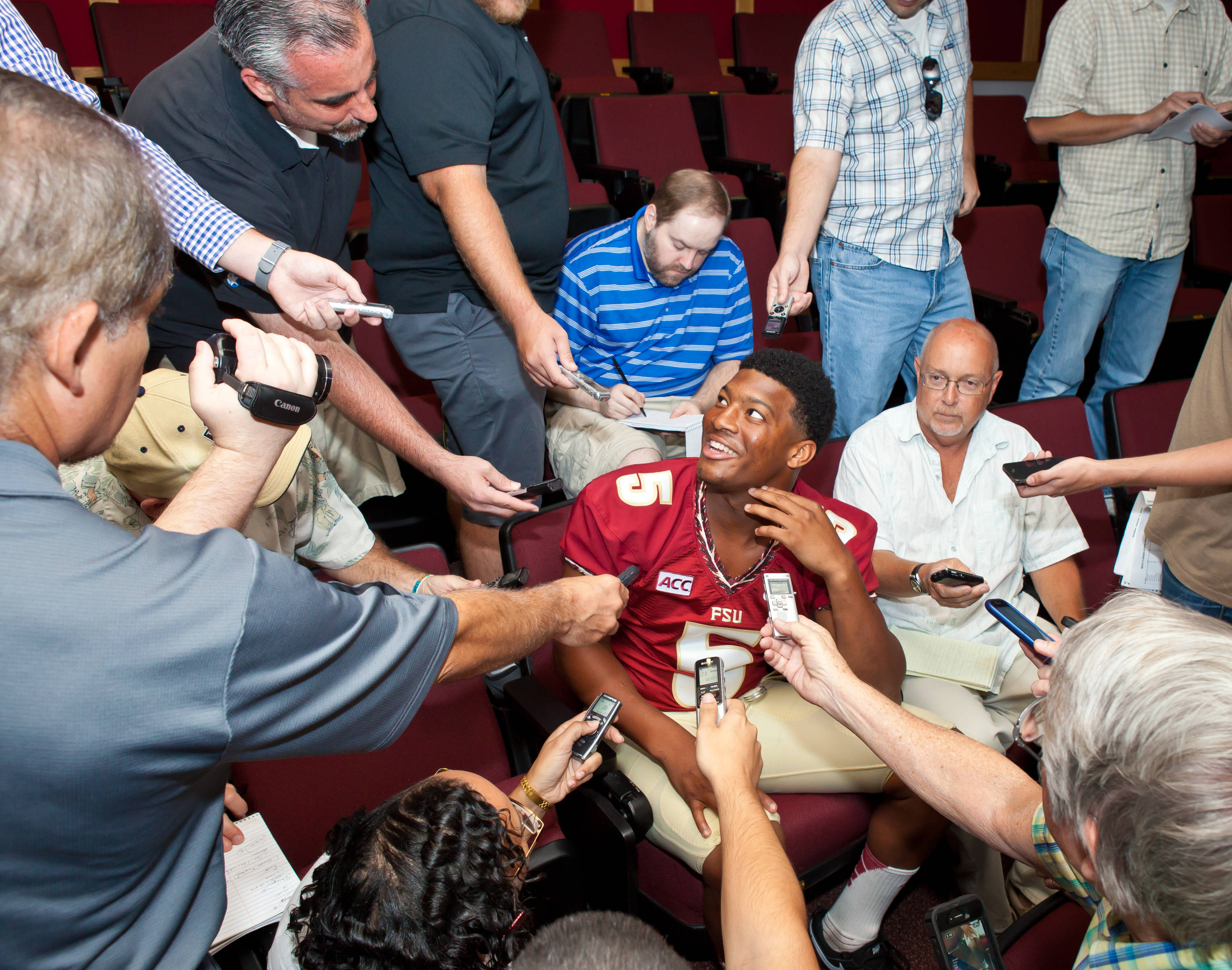 Jameis Winston is surrounded by reporters.