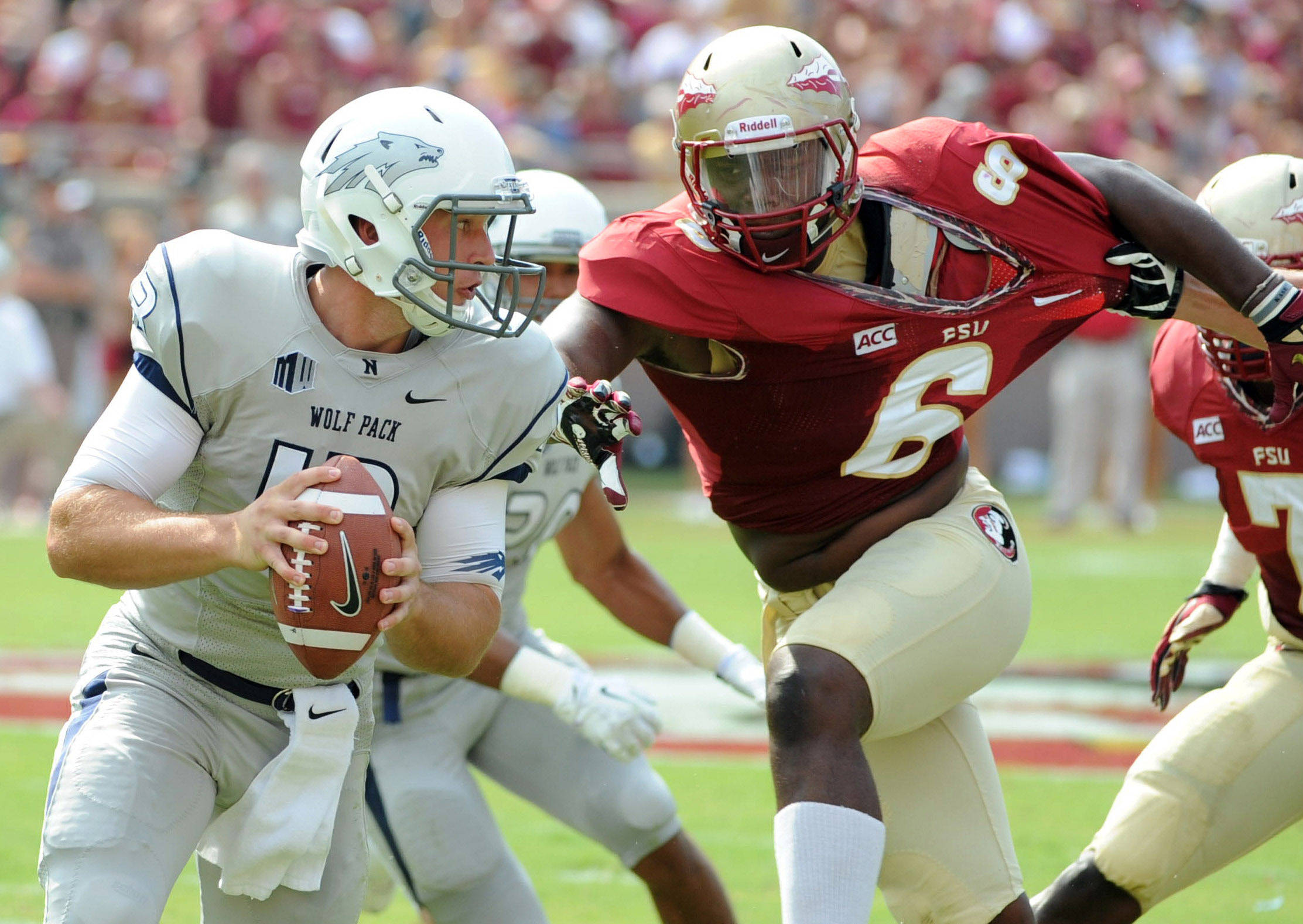 Sep 14, 2013; Tallahassee, FL, USA; Nevada Wolf Pack quarterback Devin Combs (13) runs the ball as he is pressured by Florida State Seminoles defensive end Dan Hicks (6) during the first half of the game at Doak Campbell Stadium. Mandatory Credit: Melina Vastola-USA TODAY Sports