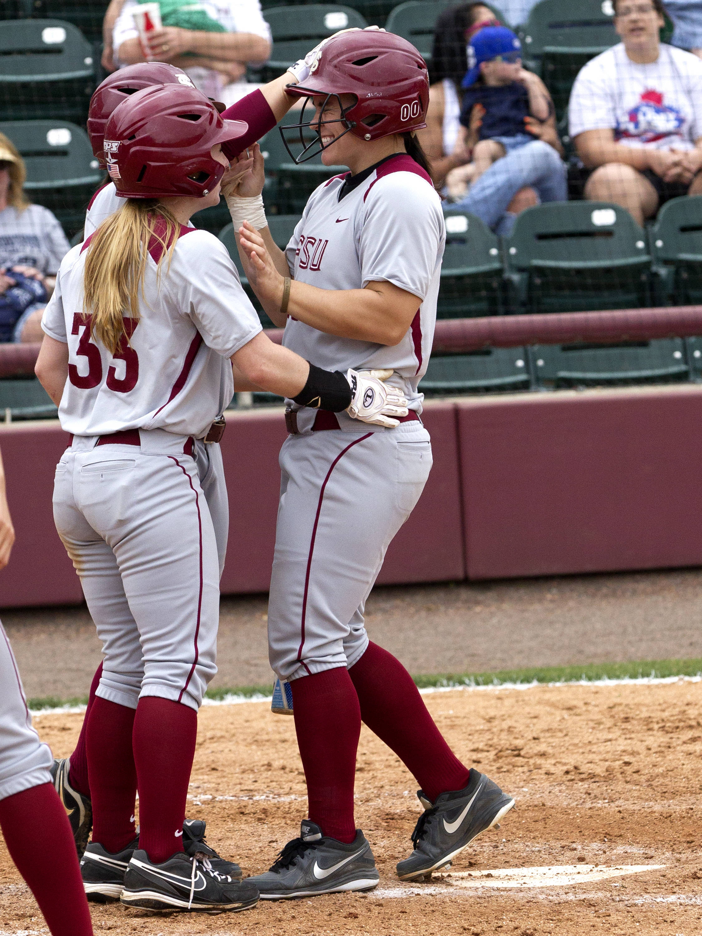 Celeste Gomez (00) being welcomed crossing home plate, FSU vs Minnesota, 03/17/13. (Photo by Steve Musco)